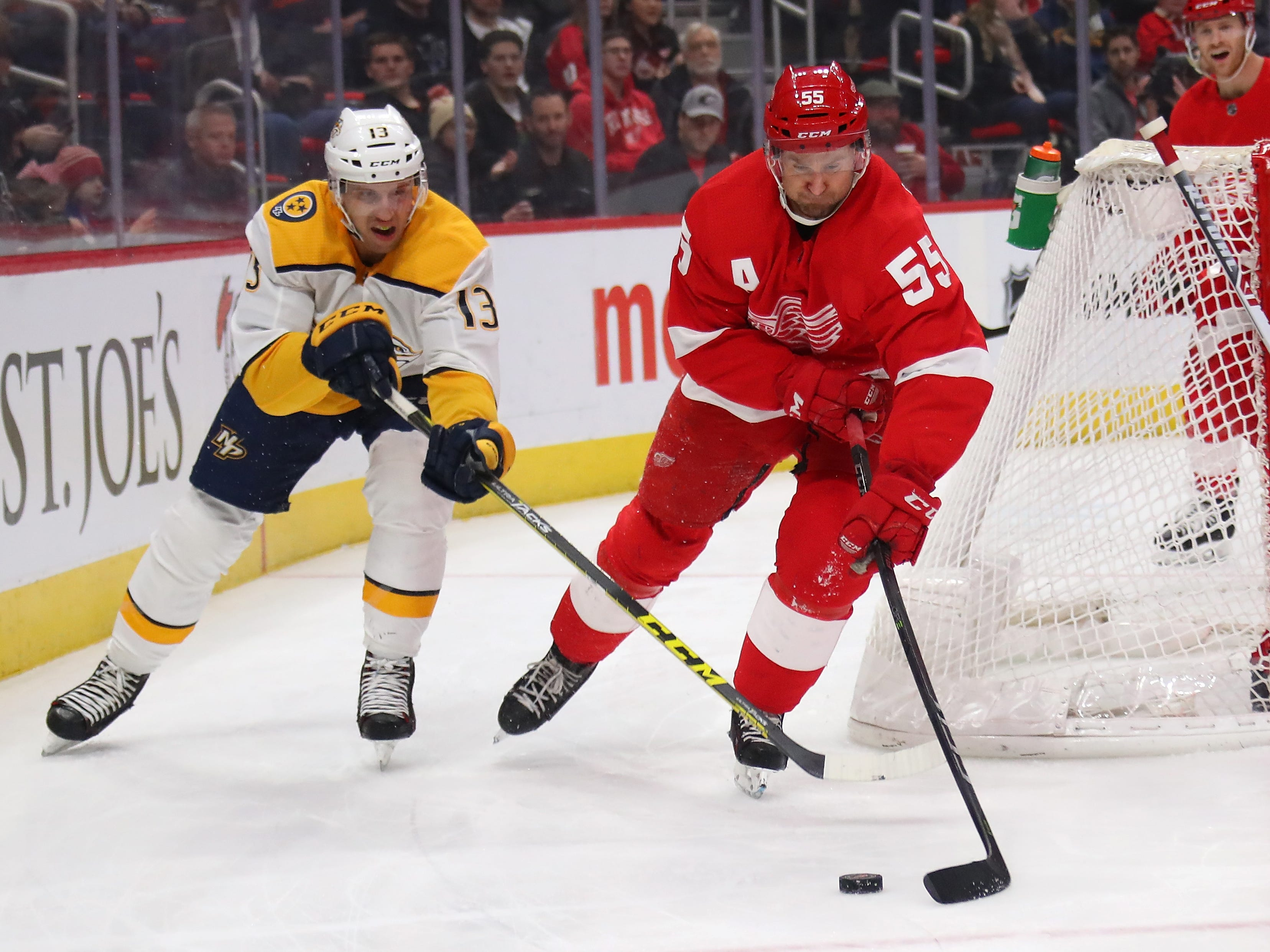 Red Wings' Niklas Kronwall (55) tries to control the puck next to Predators' Nick Bonino (13) during the first period.