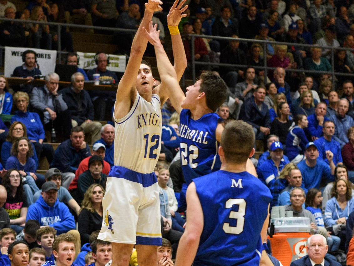 Castle's Alex Hemenway (12) shoots a three-pointer over Memorial's Mason Auker (22) during the second quarter at Castle High School in Newburgh, Ind., Friday, Jan. 4, 2019.