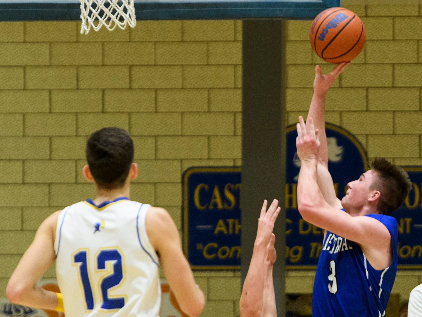 Memorial's Branson Combs (3) knocks over Castle's Bob Nunge (20) while attempting a shot during the second quarter at Castle High School in Newburgh, Ind., Friday, Jan. 4, 2019. The Knights defeated the Tigers, 72-43.