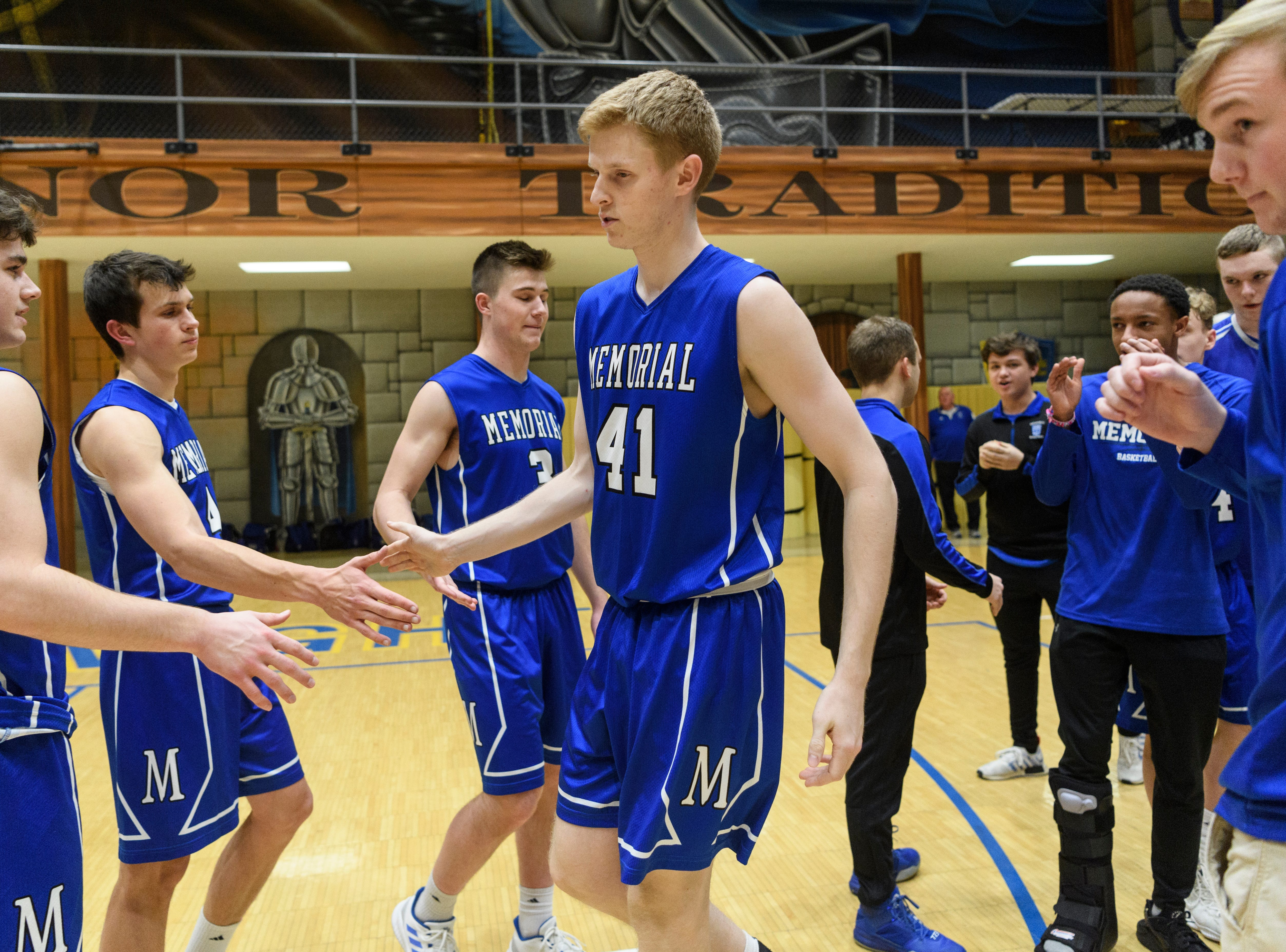 Memorial's Sam DeVault (41) high-fives his teammates after being introduced as a starter before the game against the Castle Knights at Castle High School in Newburgh, Ind., Friday, Jan. 4, 2019. The Knights defeated the Tigers, 72-43.