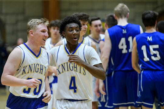 Castle's Brycen Moore (30) and Isaiah Swope (4) react to their 72-43 win over the Memorial Tigers while walking back to the locker room at Castle High School in Newburgh, Ind., Friday, Jan. 4, 2019.