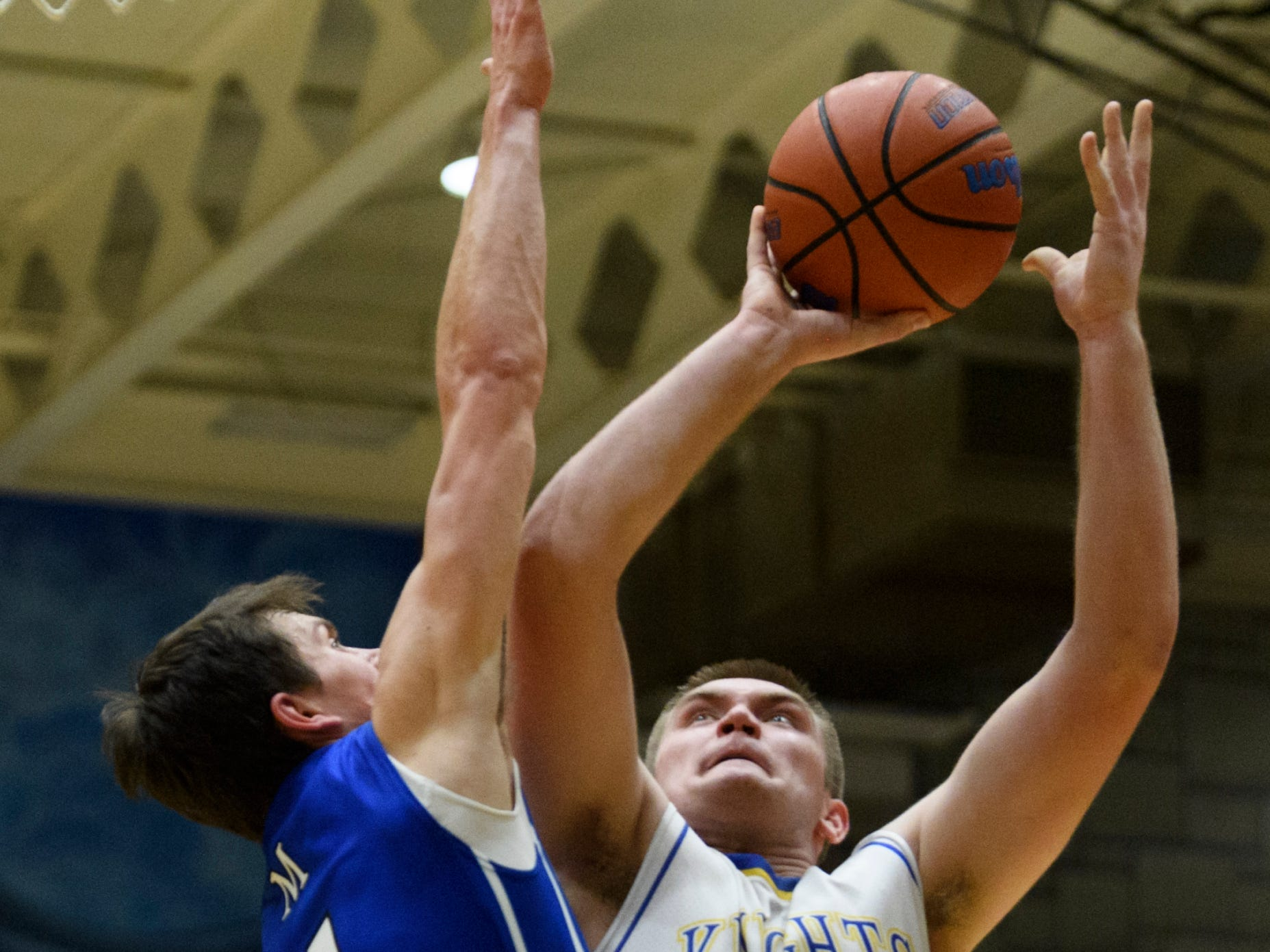 Memorial's Justin Waiz (4) blocks Castle's Brodey Heaton (44) from the net during the fourth quarter at Castle High School in Newburgh, Ind., Friday, Jan. 4, 2019. The Knights defeated the Tigers, 72-43.