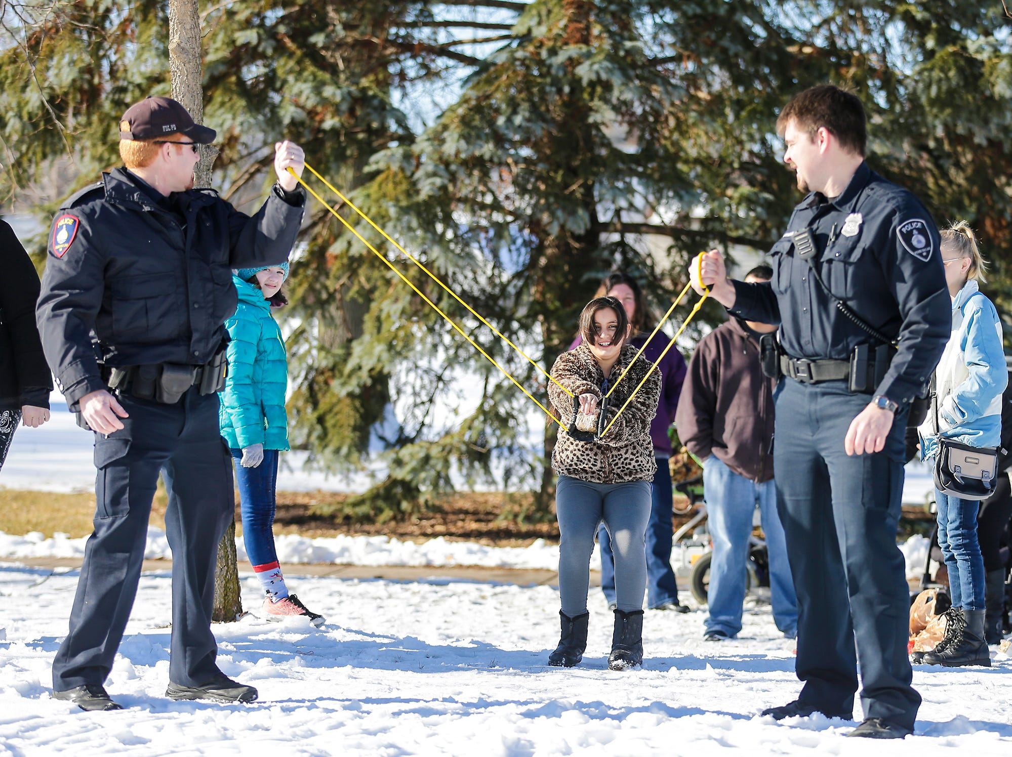 Fond du Lac Police officers Shawn Provot and Matt Chevremont hold a sling shot as Lita Basina winds up to launch a fruit cake at Winterfest Saturday, January 5, 2019 at Hamilton park in Fond du Lac, Wisconsin. Doug Raflik/USA TODAY NETWORK-Wisconsin