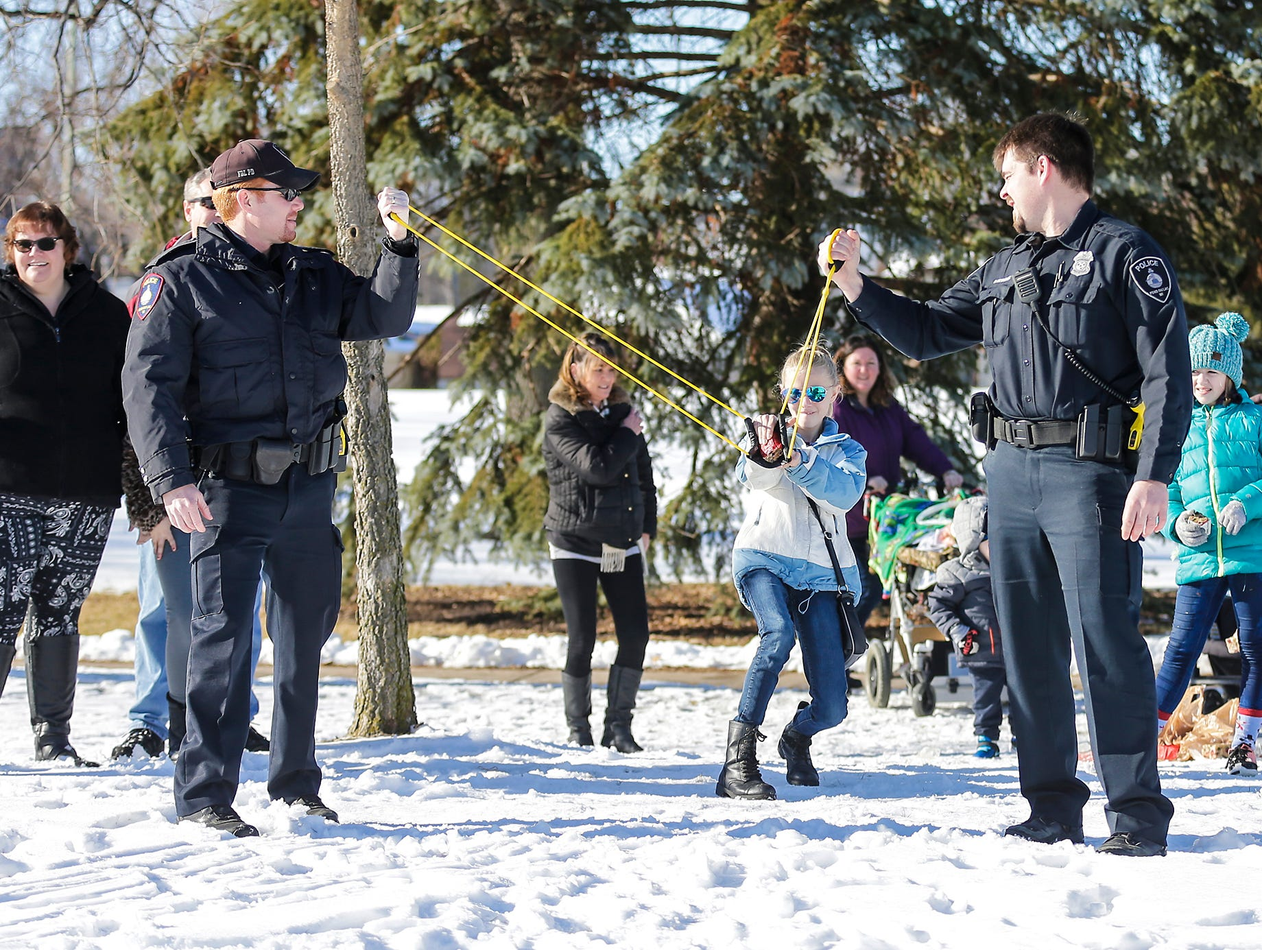 Fond du Lac Police officers Shawn Provot and Matt Chevremont hold a sling shot as Madi Bush winds up to launch a fruit cake at Winterfest Saturday, January 5, 2019 at Hamilton park in Fond du Lac, Wisconsin. Doug Raflik/USA TODAY NETWORK-Wisconsin