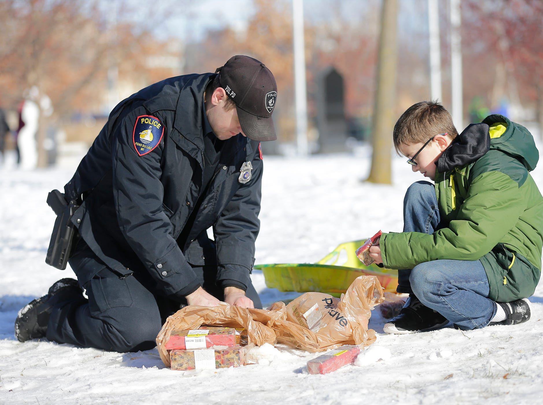 Fond du Lac Police Officer Erik Foster and Declan O'Connor of Fond du lac prepare fruit cakes for the fruit cake toss at Winterfest Saturday, January 5, 2019 at Hamilton park in Fond du Lac, Wisconsin. Doug Raflik/USA TODAY NETWORK-Wisconsin
