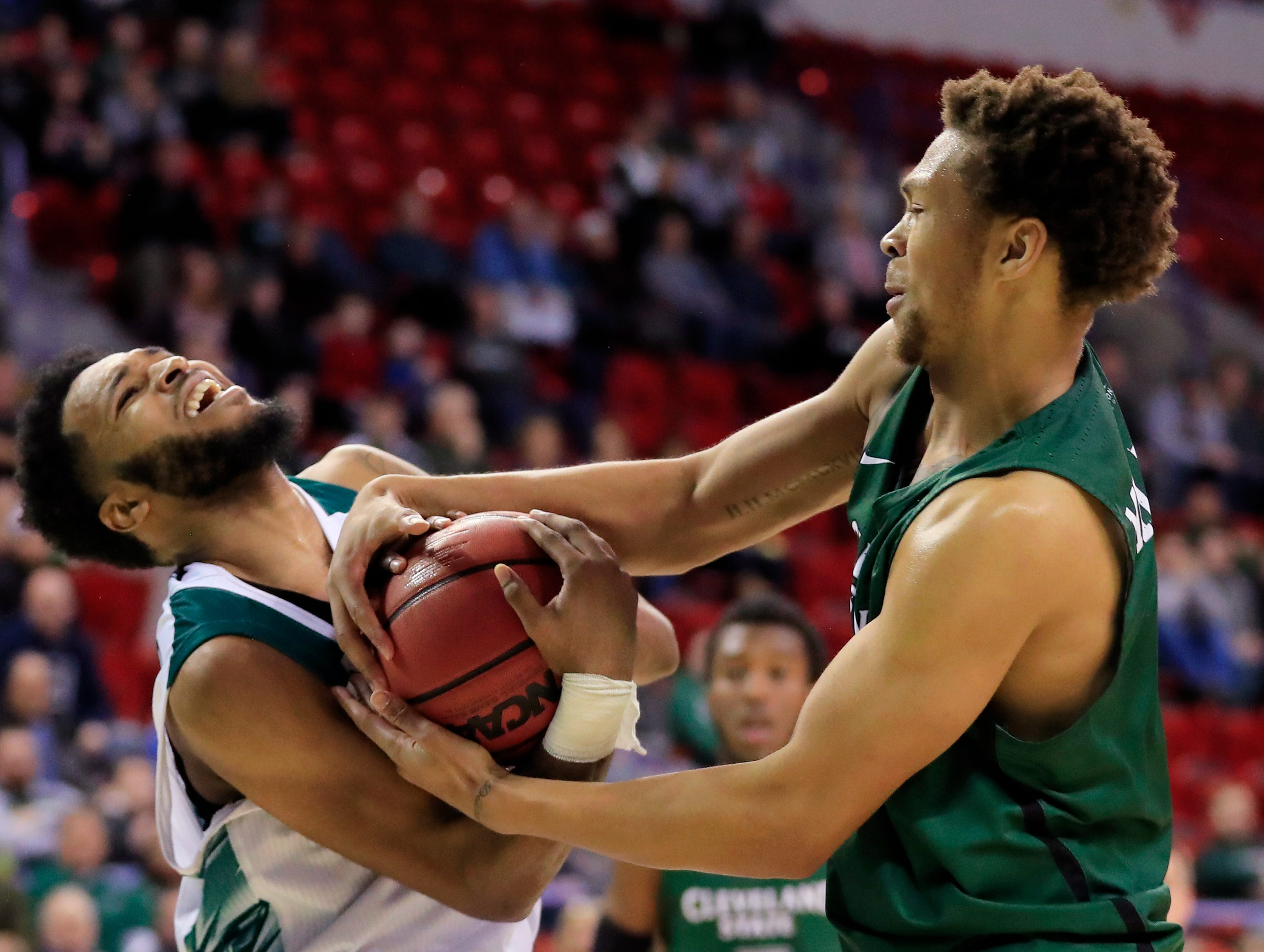 Green Bay Phoenix guard JayQuan McCloud (11) and Cleveland State Vikings forward Seth Millner (4) get tied up in a Horizon League basketball game at the Resch Center on Saturday, January 5, 2019 in Green Bay, Wis.