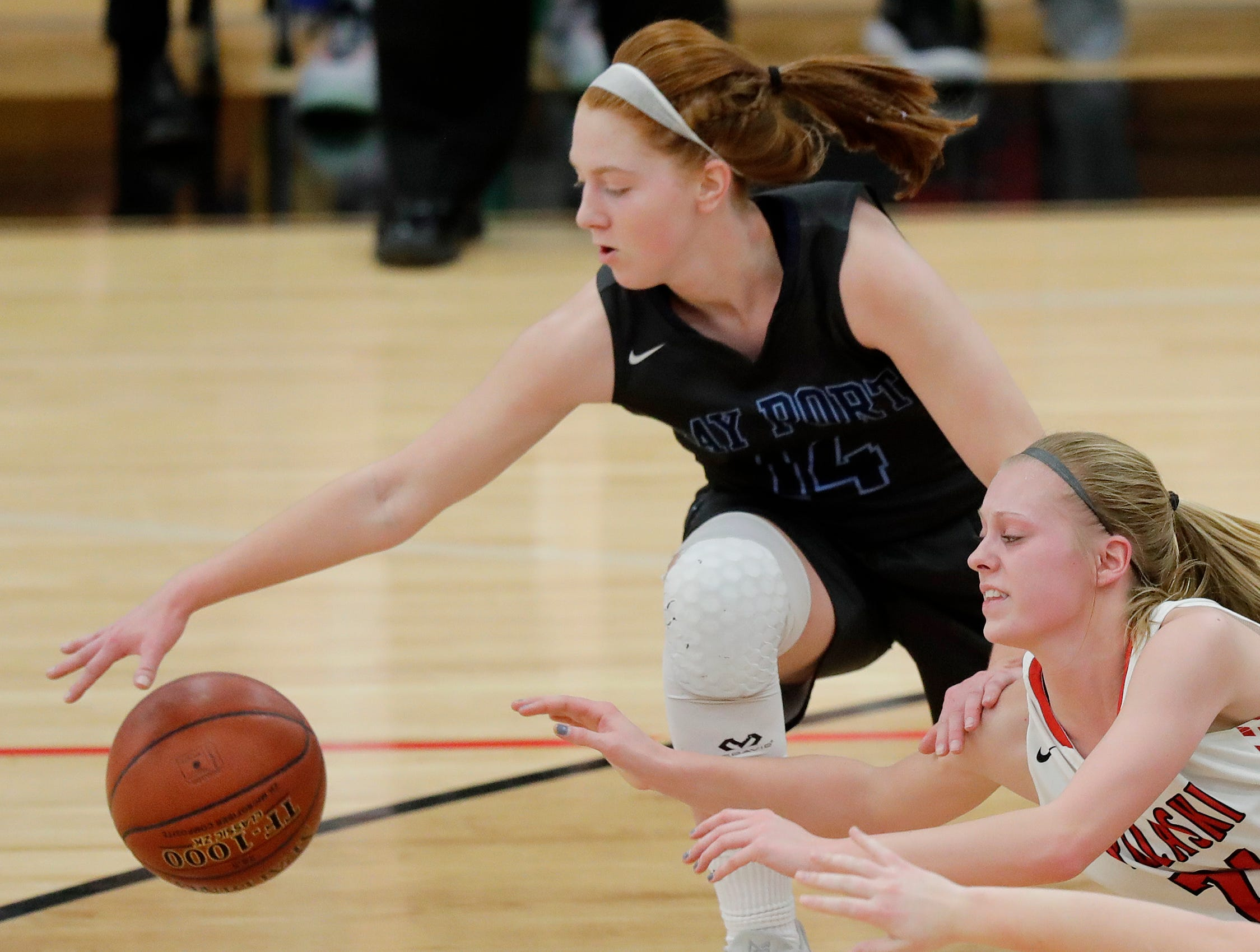 Bay Port's Alaina Abel (14) gets to a loose ball ahead of Pulaski's Chelsey Gilson (24) in a girls basketball game at Pulaski high school on Friday, January 4, 2019 in Pulaski, Wis.