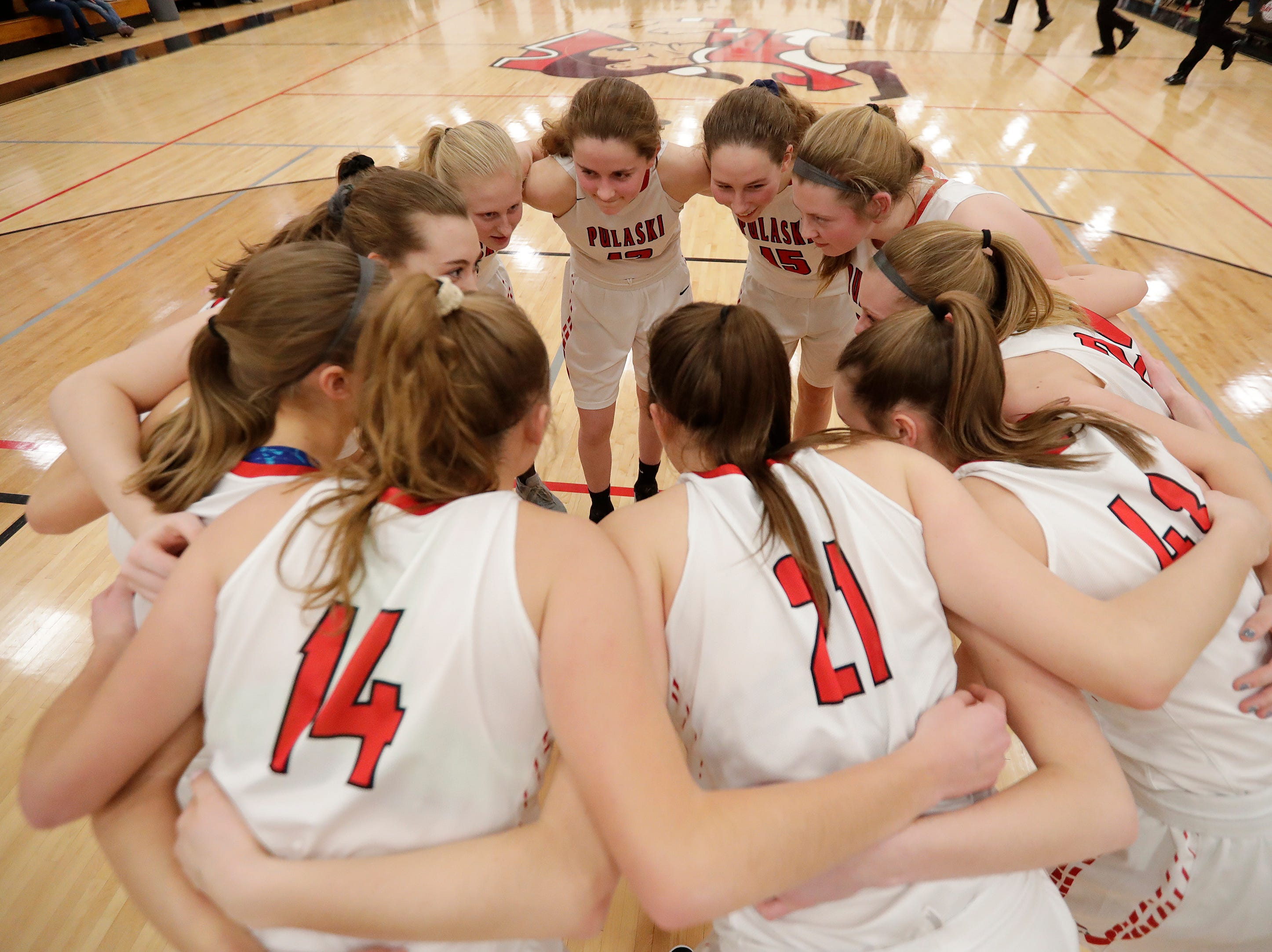 Pulaski players huddle before a girls basketball game at Pulaski high school on Friday, January 4, 2019 in Pulaski, Wis.