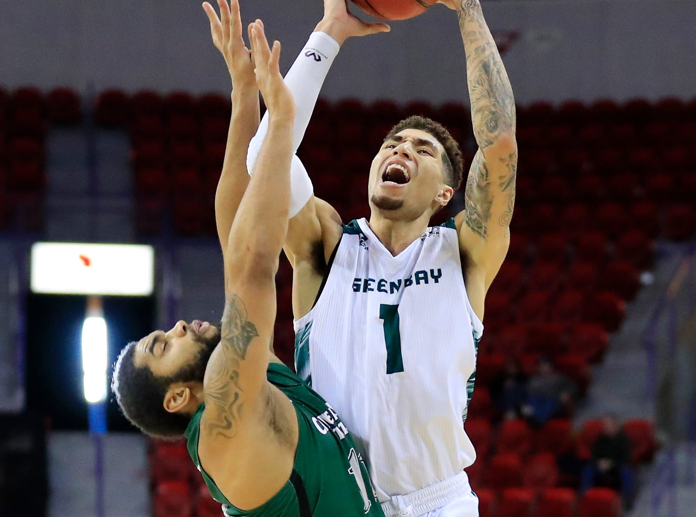 Green Bay Phoenix guard Sandy Cohen III (1) gets fouled by Cleveland State Vikings guard Dontel Highsmith (11) while shooting a three in a Horizon League basketball game at the Resch Center on Saturday, January 5, 2019 in Green Bay, Wis.