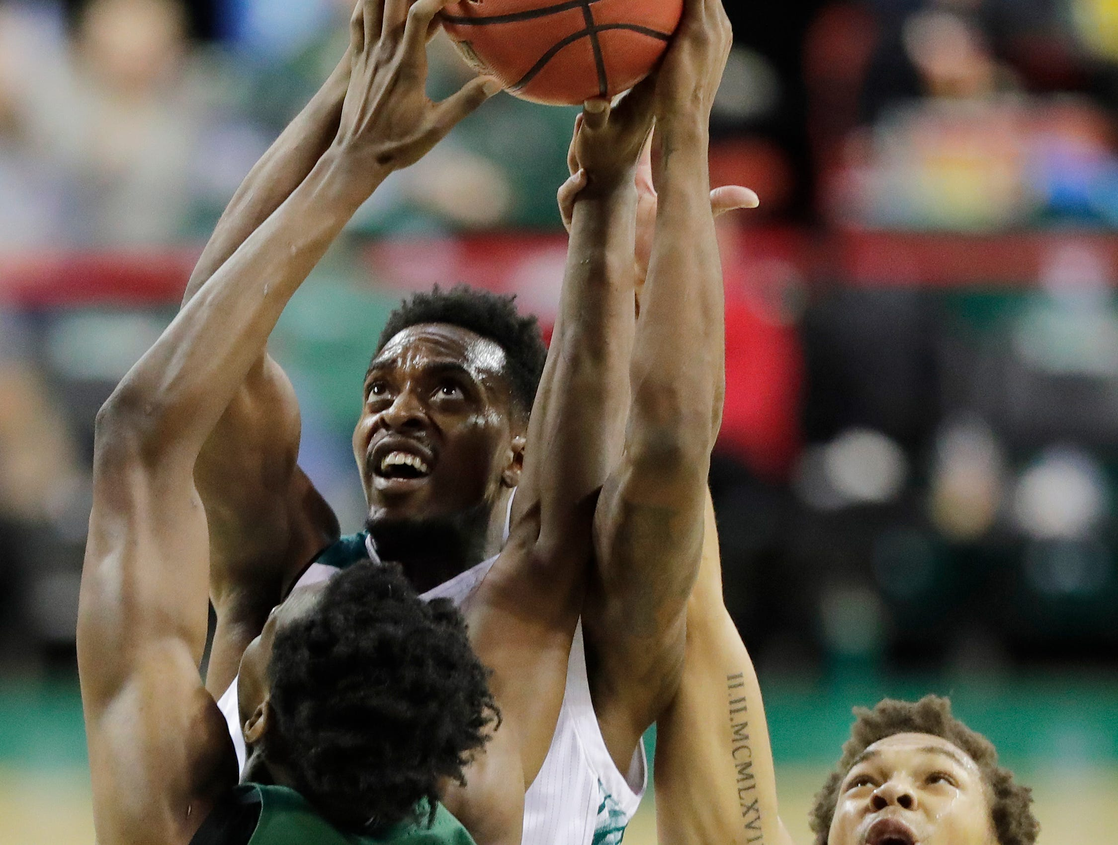 Green Bay Phoenix forward Josh McNair (12) grabs a rebound against Cleveland State Vikings forward Deante Johnson (35) and forward Seth Millner (4) in a Horizon League basketball game at the Resch Center on Saturday, January 5, 2019 in Green Bay, Wis.