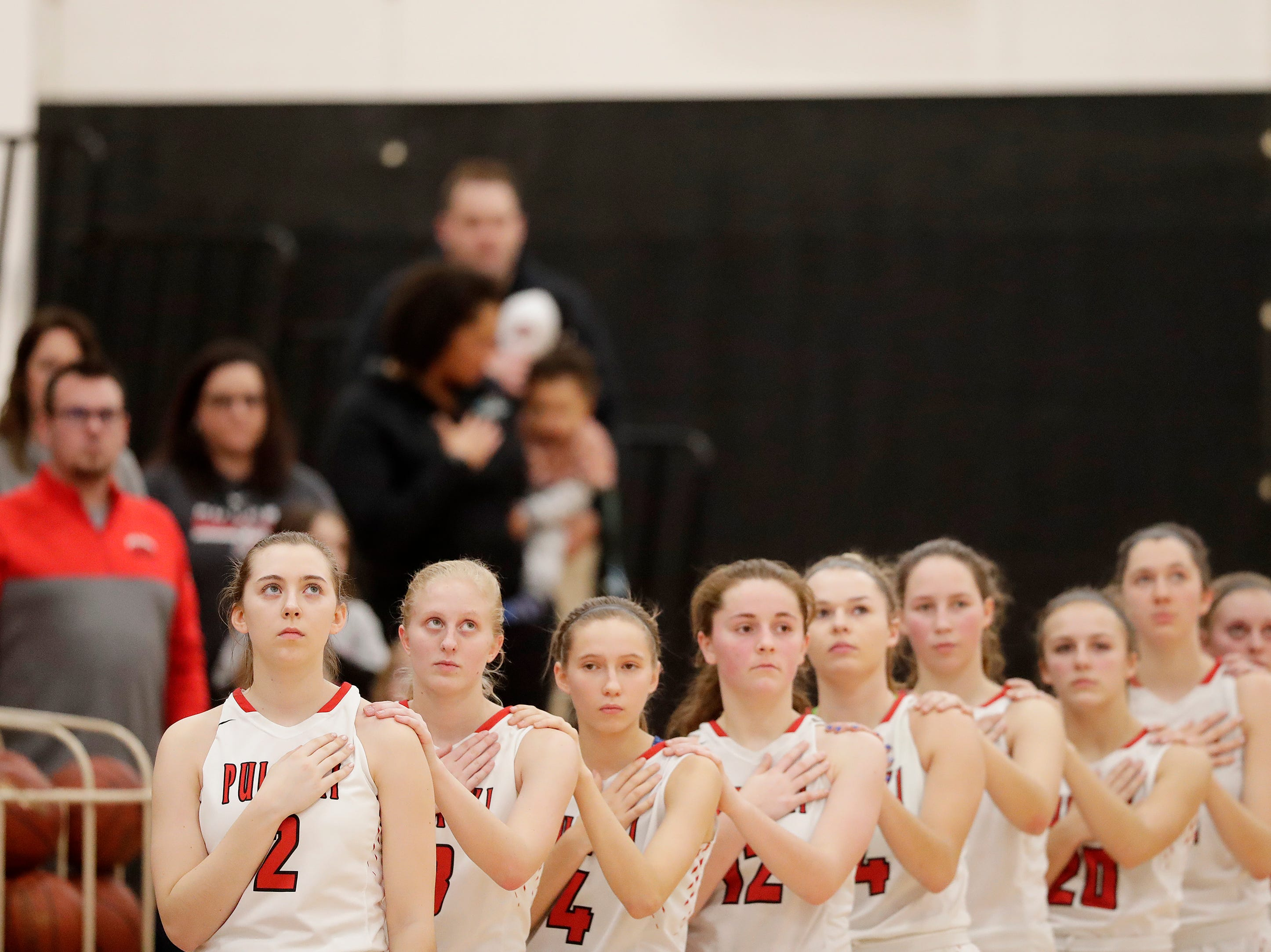 Pulaski players lineup for the anthem before a game against Bay Port at Pulaski high school on Friday, January 4, 2019 in Pulaski, Wis.