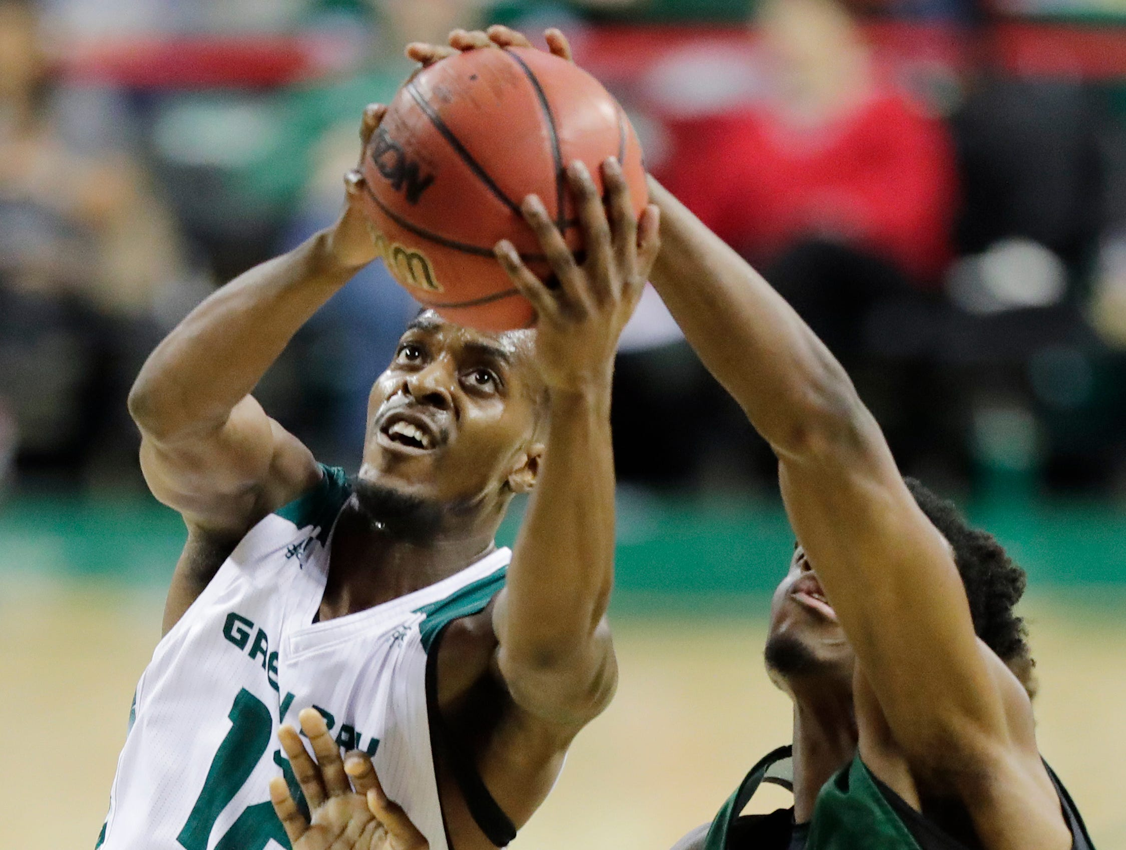 Green Bay Phoenix forward Josh McNair (12) drives to the basket against Cleveland State Vikings forward Deante Johnson (35) in a Horizon League basketball game at the Resch Center on Saturday, January 5, 2019 in Green Bay, Wis.