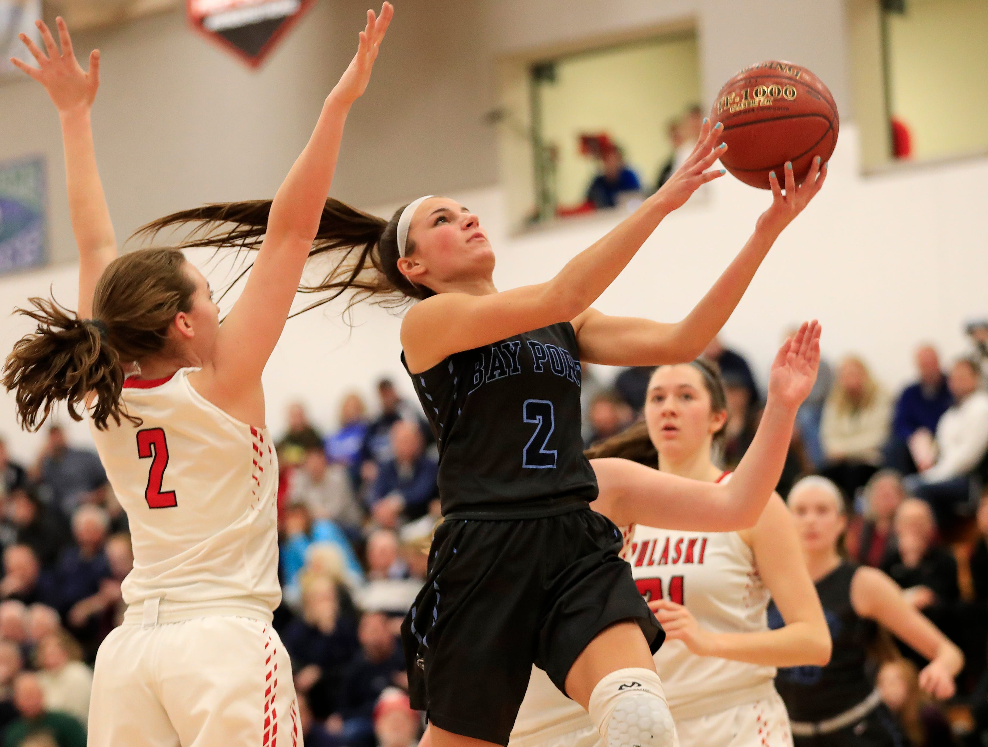 Bay Port's Grace Krause (2) scores past Pulaski's Isabel Majewski (2) in a girls basketball game at Pulaski high school on Friday, January 4, 2019 in Pulaski, Wis.