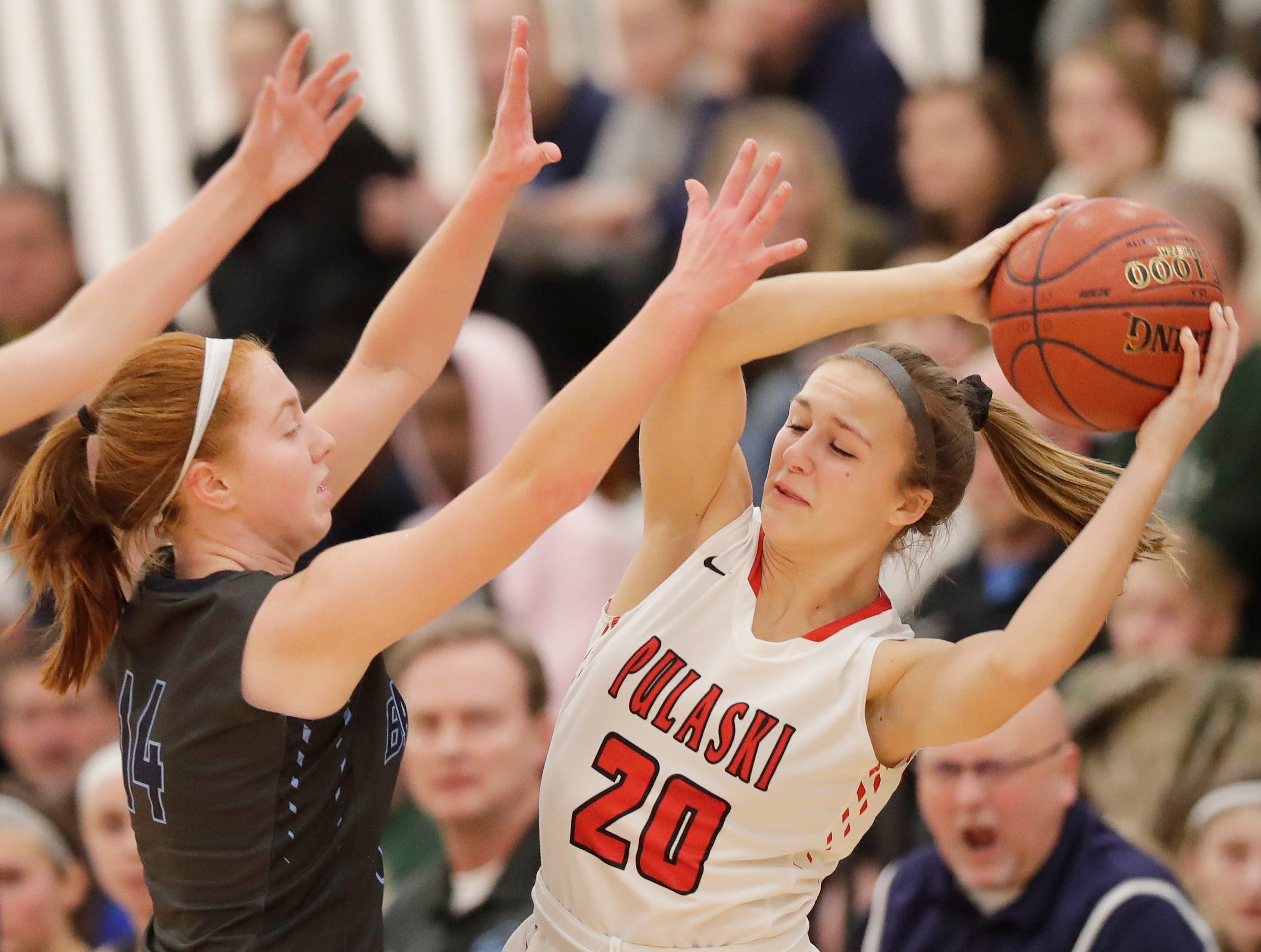 Pulaski's Ashlyn Szymanski (20) is pressured by Alaina Abel (14) in a girls basketball game at Pulaski high school on Friday, January 4, 2019 in Pulaski, Wis.