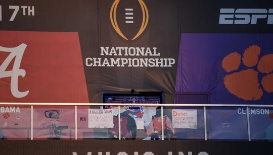 Fans for Alabama and Clemson campout on a billboard in downtown San Jose, watching ESPN on a television January 4, 2019.