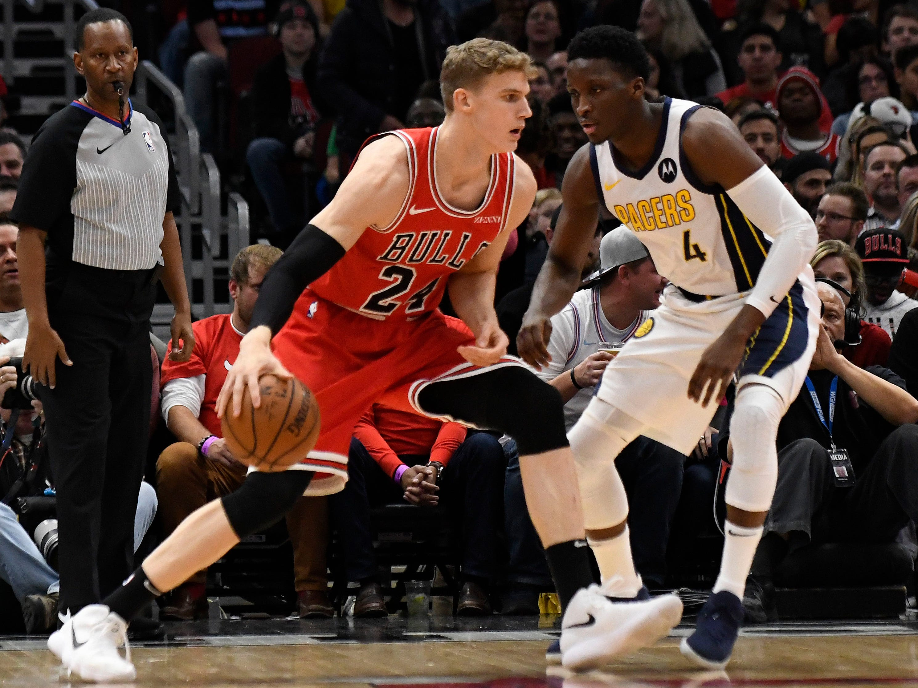 Chicago Bulls forward Lauri Markkanen (24) is defended by Indiana Pacers guard Victor Oladipo (4) during the first half at United Center.