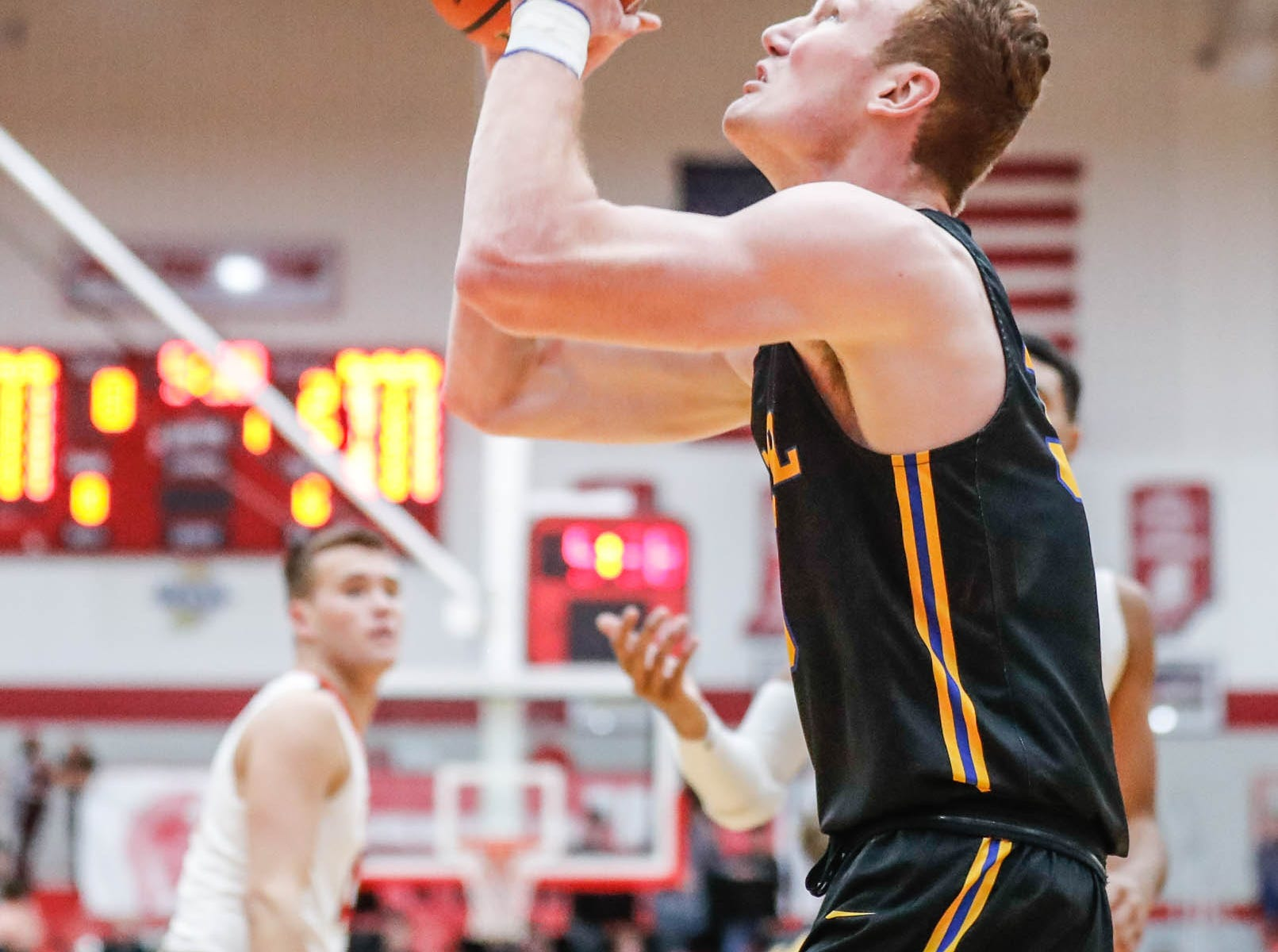 Carmel High School's John Michael Mulloy (33) shoots for the hoop during a game between Center Grove High School and Carmel High School, held at Center Grove on on Friday, Jan. 4, 2019.