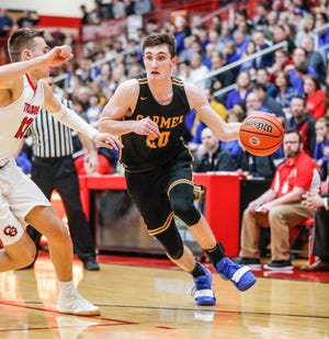 Carmel High School's Andrew Owens (20), dribbles around Center Grove High School's forward Justin DeGraaf (13), during a game between Center Grove High School and Carmel High School, held at Center Grove on on Friday, Jan. 4, 2019.