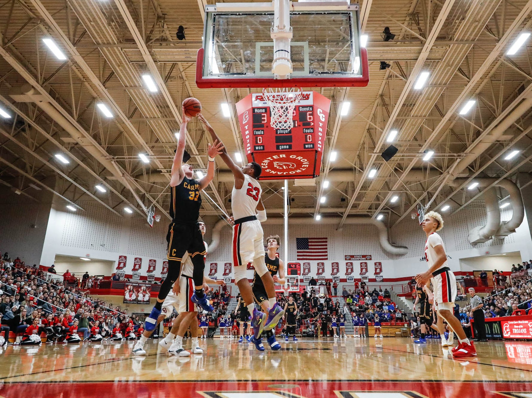Center Grove High School's forward Trayce Jackson-Davis (23) attempts to block a shot by Carmel High School's John Michael Mulloy (33), during a game between Center Grove High School and Carmel High School, held at Center Grove on on Friday, Jan. 4, 2019.