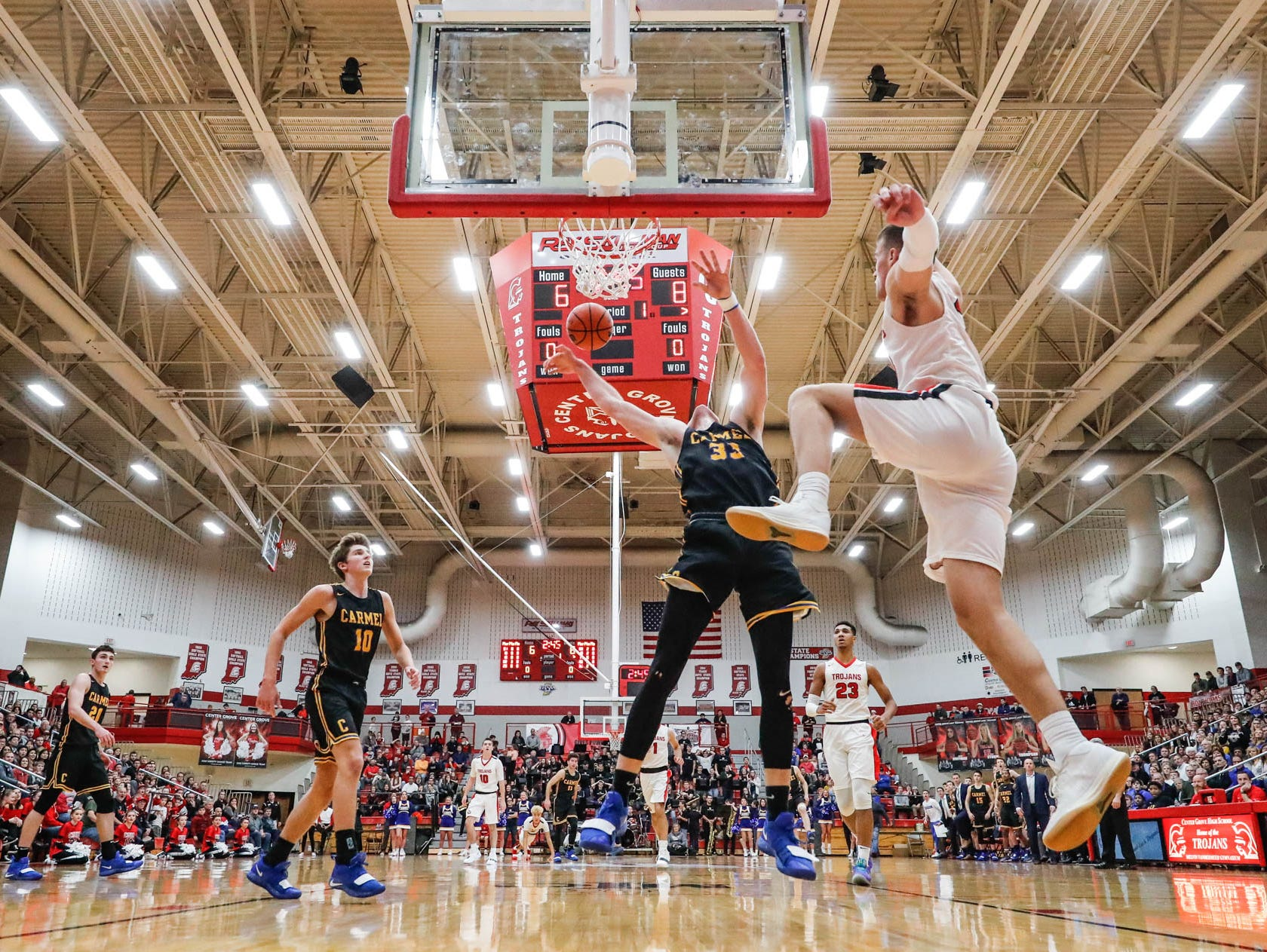 Center Grove High School's forward Justin DeGraaf (13) attempts to block a shot by Carmel High School's John Michael Mulloy (33), during a game between Center Grove High School and Carmel High School, held at Center Grove on on Friday, Jan. 4, 2019.