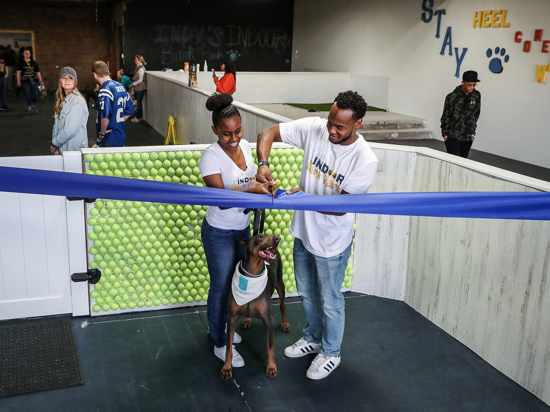 From left, Danielle and Darius Smith and their dog King cut a ribbon marking grand opening of Indy's Indoor Bark Park in Indianapolis, Saturday, Jan, 5, 2019. The large indoor space offers owners a place to exercise their dogs regardless of the weather. Membership options include single-day, multi-day and annual passes.