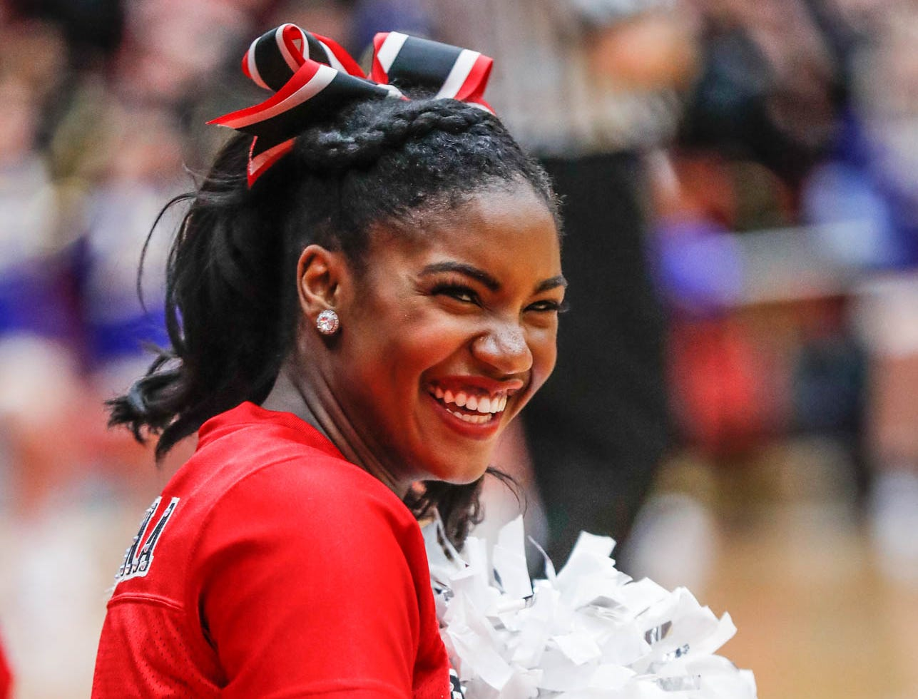 A Center Grove Dance Team member smiles at a team mate during a game between Center Grove High School and Carmel High School, held at Center Grove on on Friday, Jan. 4, 2019.