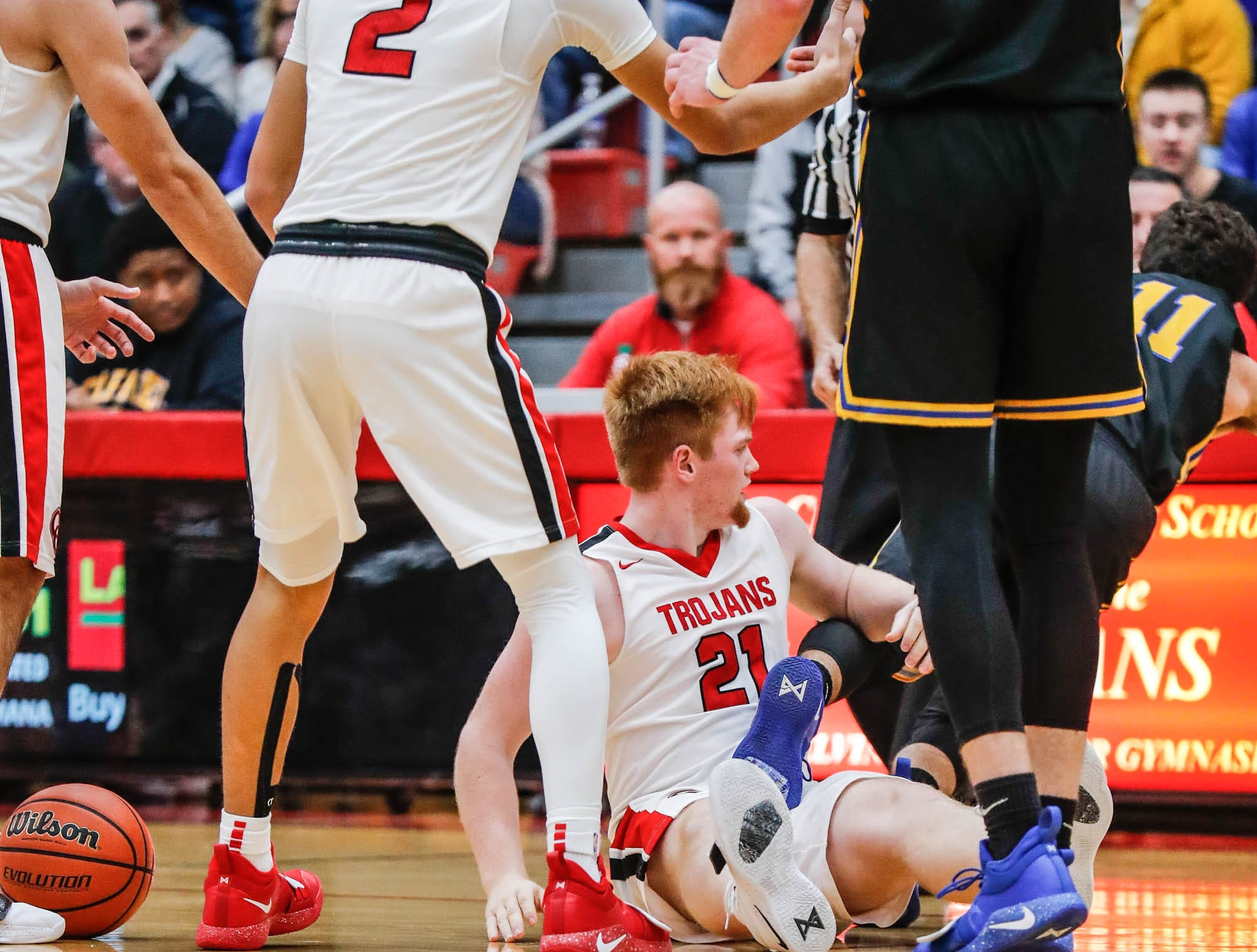 Carmel High School's Luke Heady (11) is tripped by Center Grove High School's forward Cameron Petty (21), after stepping on him in a scuffle for the ball, during a game between Center Grove High School and Carmel High School, held at Center Grove on on Friday, Jan. 4, 2019. A technical foul was called on Carmel High School's Luke Heady (11).