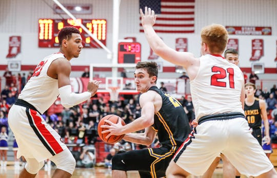 Carmel's Andrew Owens (20), boxes out against Center Grove's Trayce Jackson-Davis (23), and  Cameron Petty (21), during a game Jan. 4 at Center Grove.