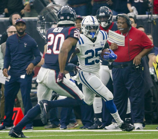 Indianapolis Colts running back Marlon Mack (25) runs the ball along the sideline as Houston Texans strong safety Justin Reid (20) closes in on him during the first half of an NFL Wild Card Round playoff game, Saturday, Jan. 5, 2019 at NRG Stadium in Houston, Texas.
