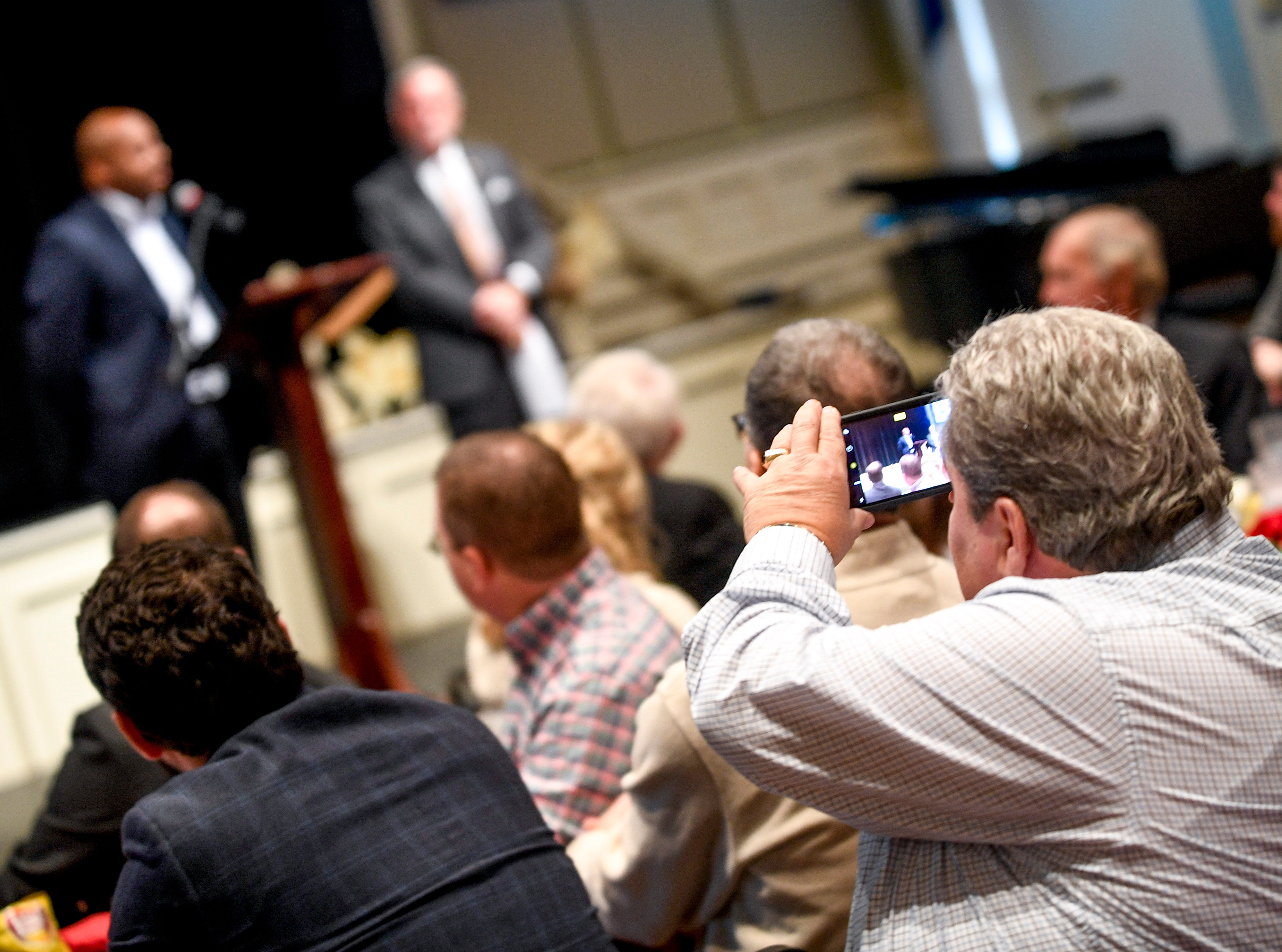 A guest takes a photo of Dr Eric Jones, JMCSS superintendent, and Madison County Mayor Jimmy Harris speak during the monthly First Friday Forum at First United Methodist Church in Jackson, Tenn., on Friday, Jan. 4, 2019.