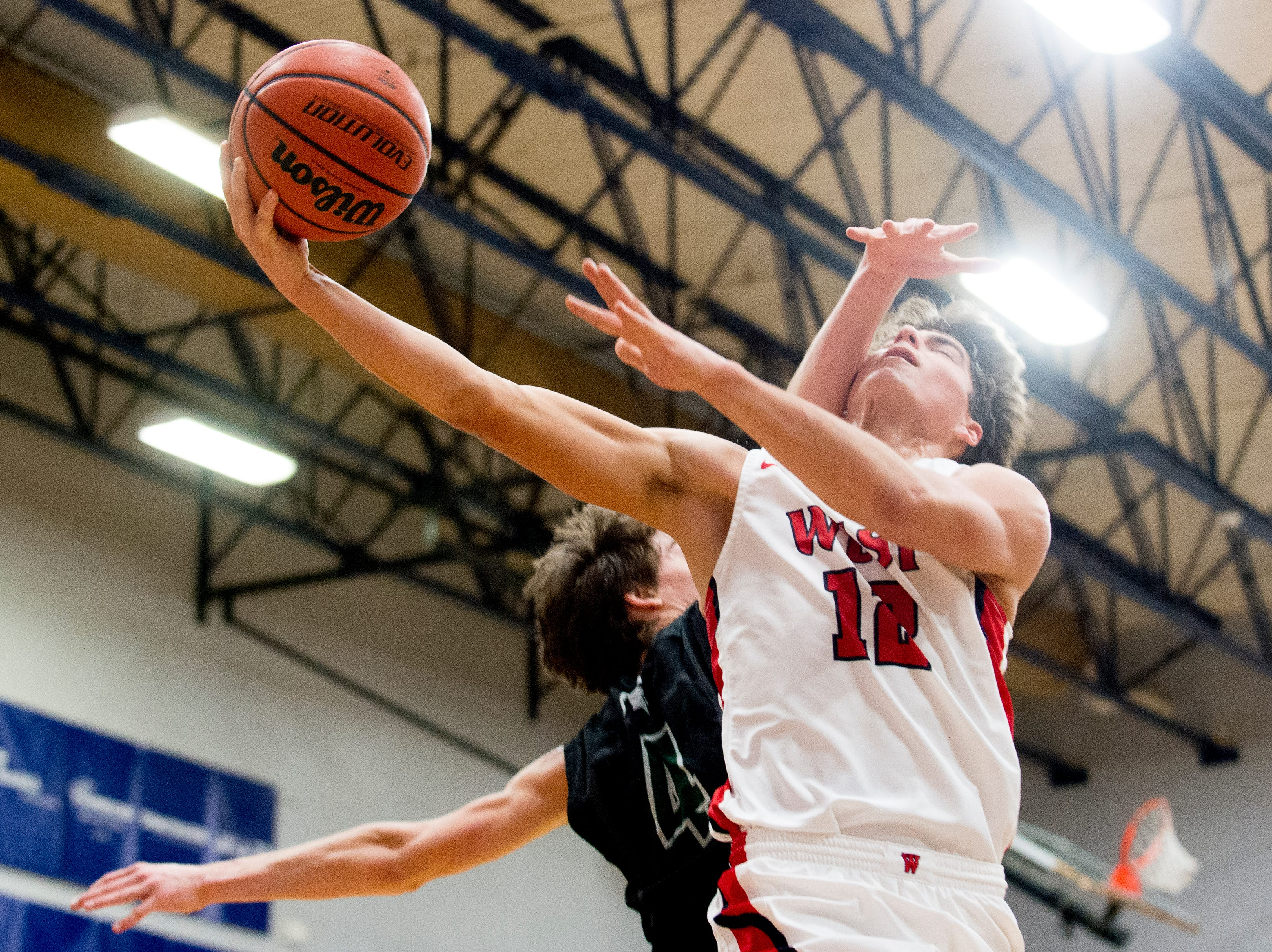 West's Will Eggleston (12) is hit in the face by Webb's Charlie Wynck (4) while going for a layup during a game between West and Webb at West High School in Knoxville, Tennessee on Friday, January 4, 2019.