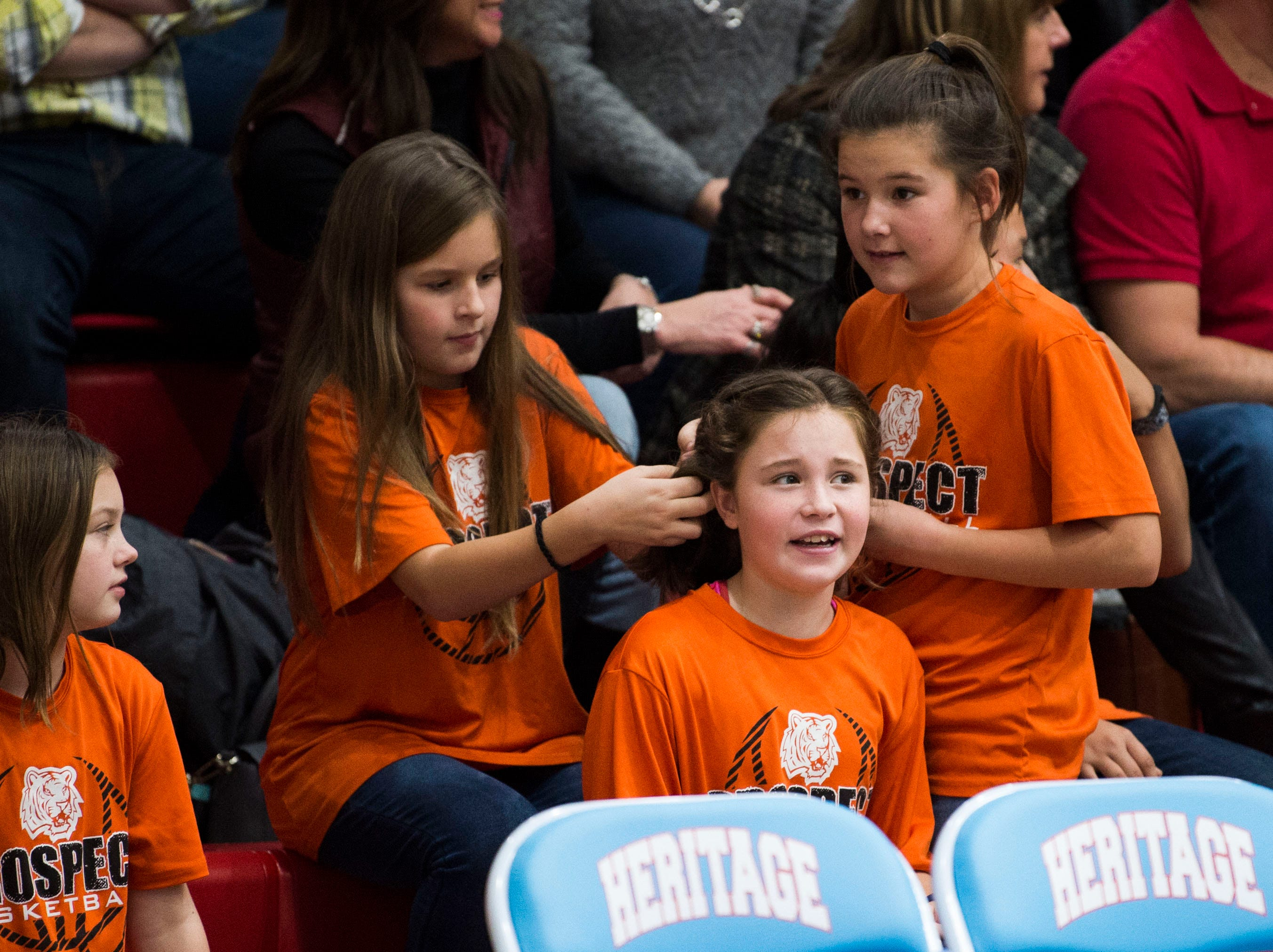 At center Faith Morris, 10, has her hair done by Kenley Coker, 10, and Ella Robertson, 10, during a high school basketball game between Maryville and Heritage at Heritage Friday, Jan. 4, 2019. Both Maryville boys and girls teams beat Heritage.