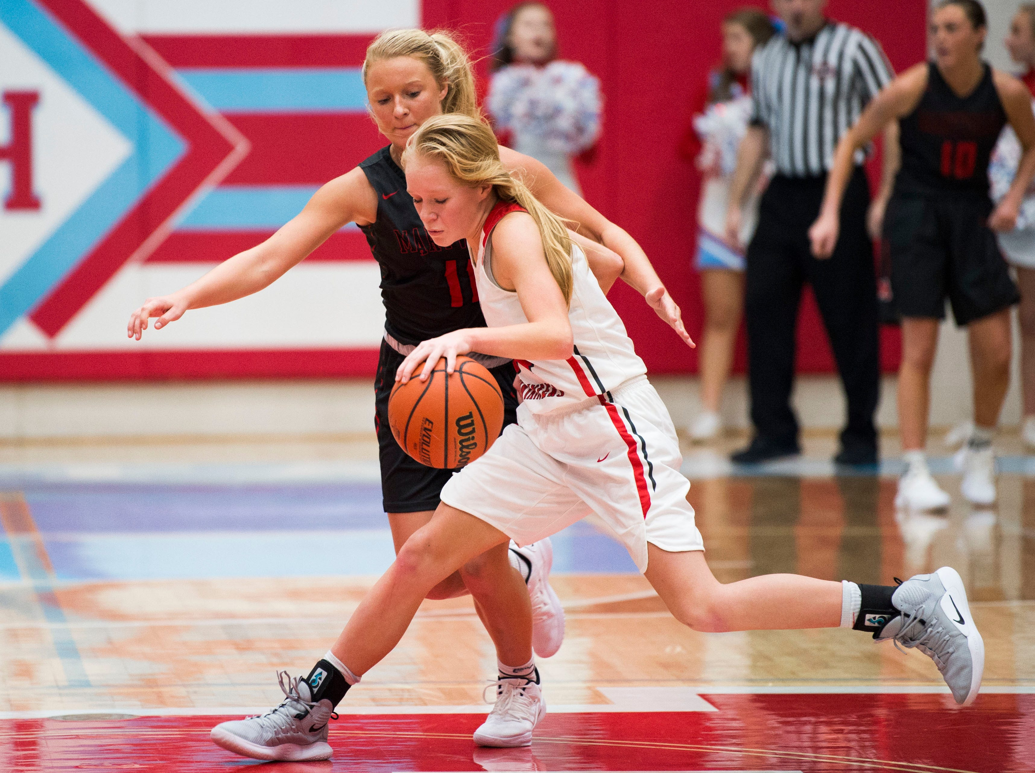 Heritage's Lexi Patty (34) dribbles the ball while defended by Maryville's Courtney Carruthers (11) during a high school basketball game between Maryville and Heritage at Heritage Friday, Jan. 4, 2019. Both Maryville boys and girls teams beat Heritage.