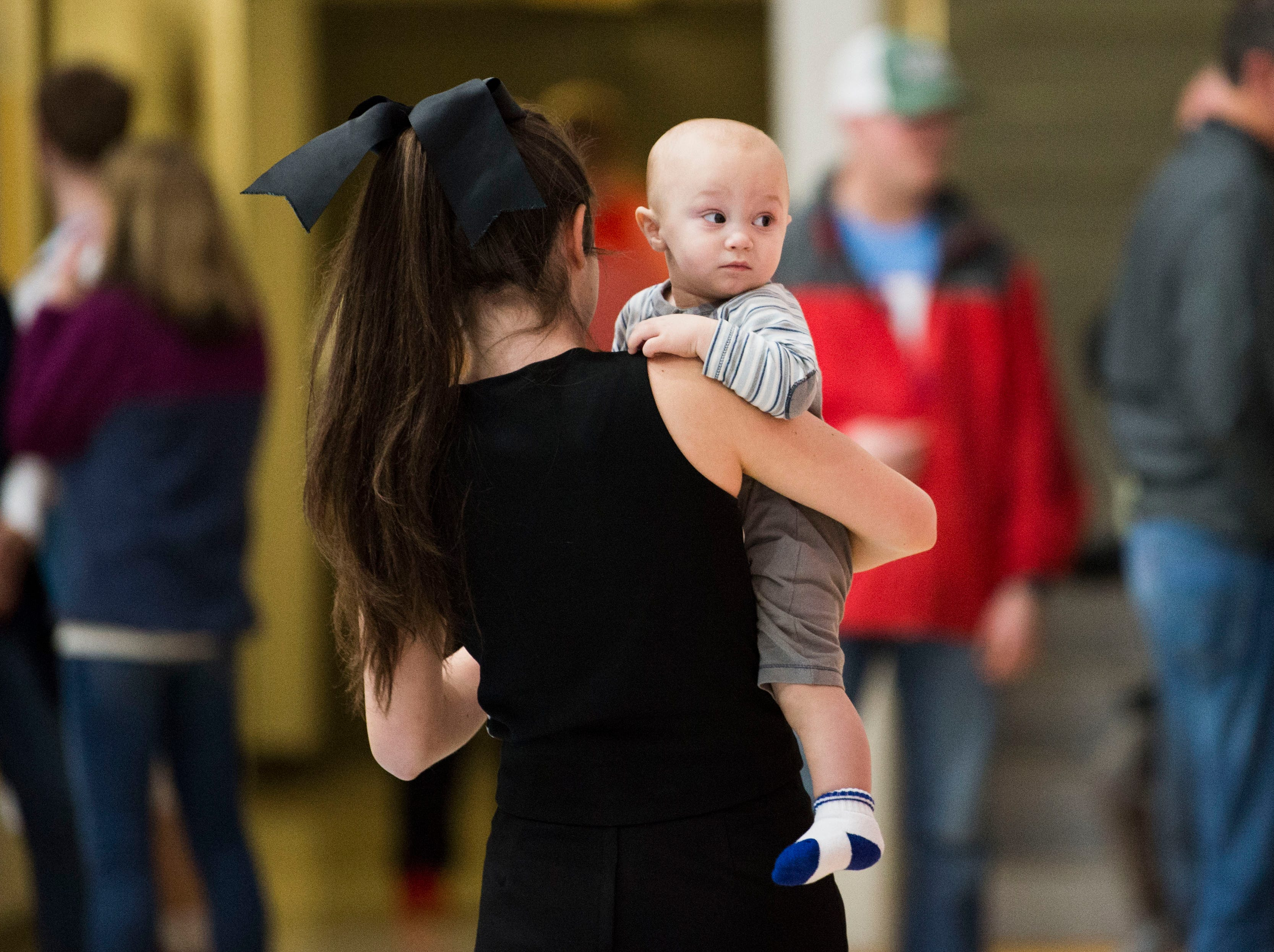 Maryville cheerleader Grace Raper carries her little brother Bryce Trentham during halftime of a high school basketball game between Maryville and Heritage at Heritage Friday, Jan. 4, 2019. Both Maryville boys and girls teams beat Heritage.