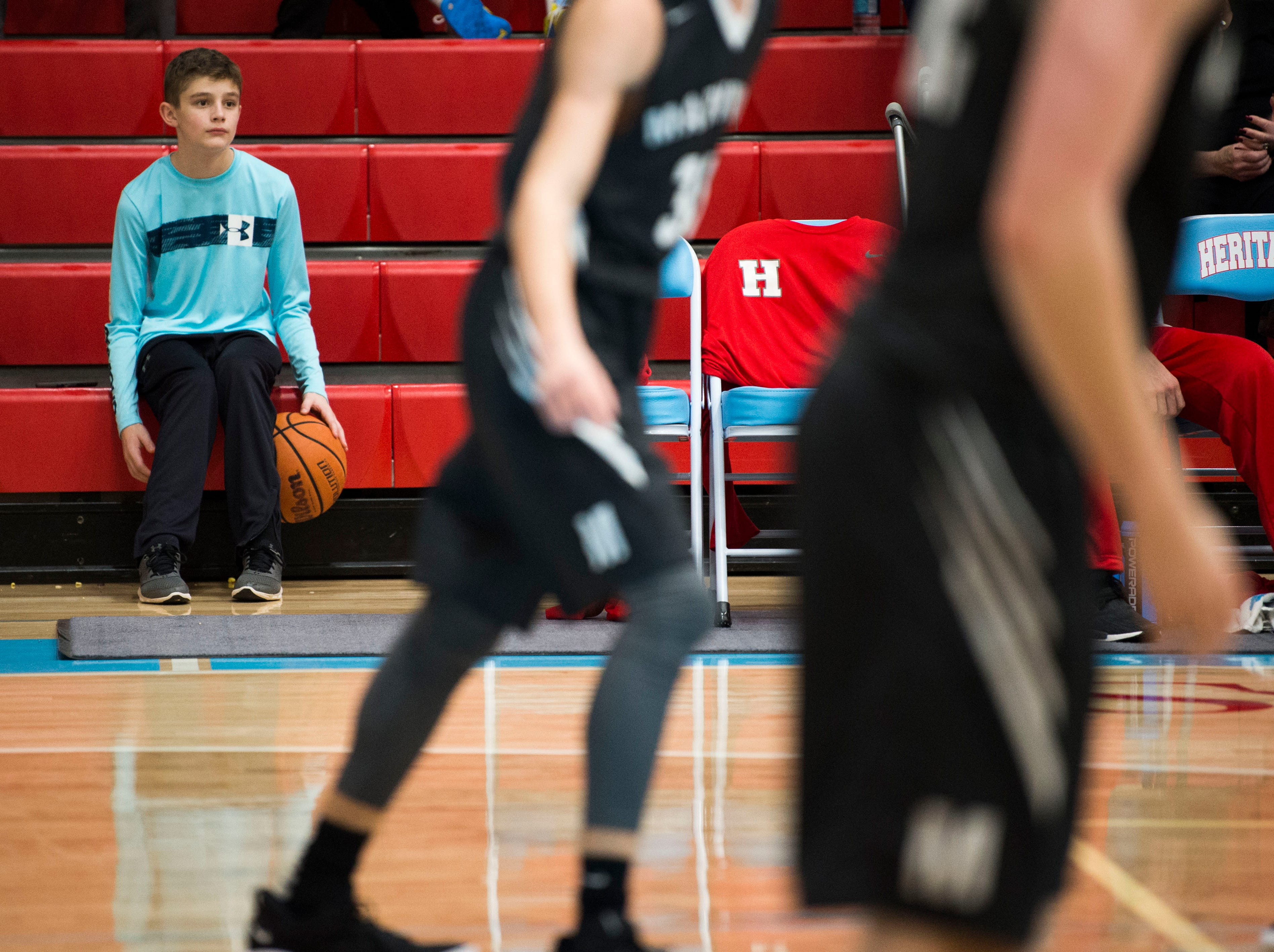 Heritage fan Parker King, 12, dribbles a ball on the bleachers during a high school basketball game between Maryville and Heritage at Heritage Friday, Jan. 4, 2019. Both Maryville boys and girls teams beat Heritage.