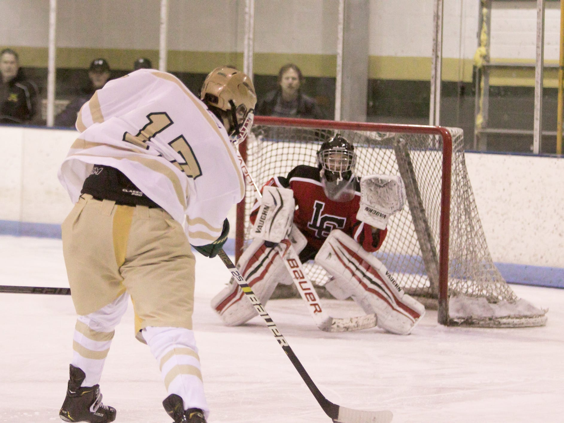 Howell's Josh Farr takes aim at Livonia Churchill goalie Justin Swamba while scoring the Highlanders' third goal in a 6-3 victory on Friday, Jan. 4, 2019 at Grand Oaks Ice Arena.