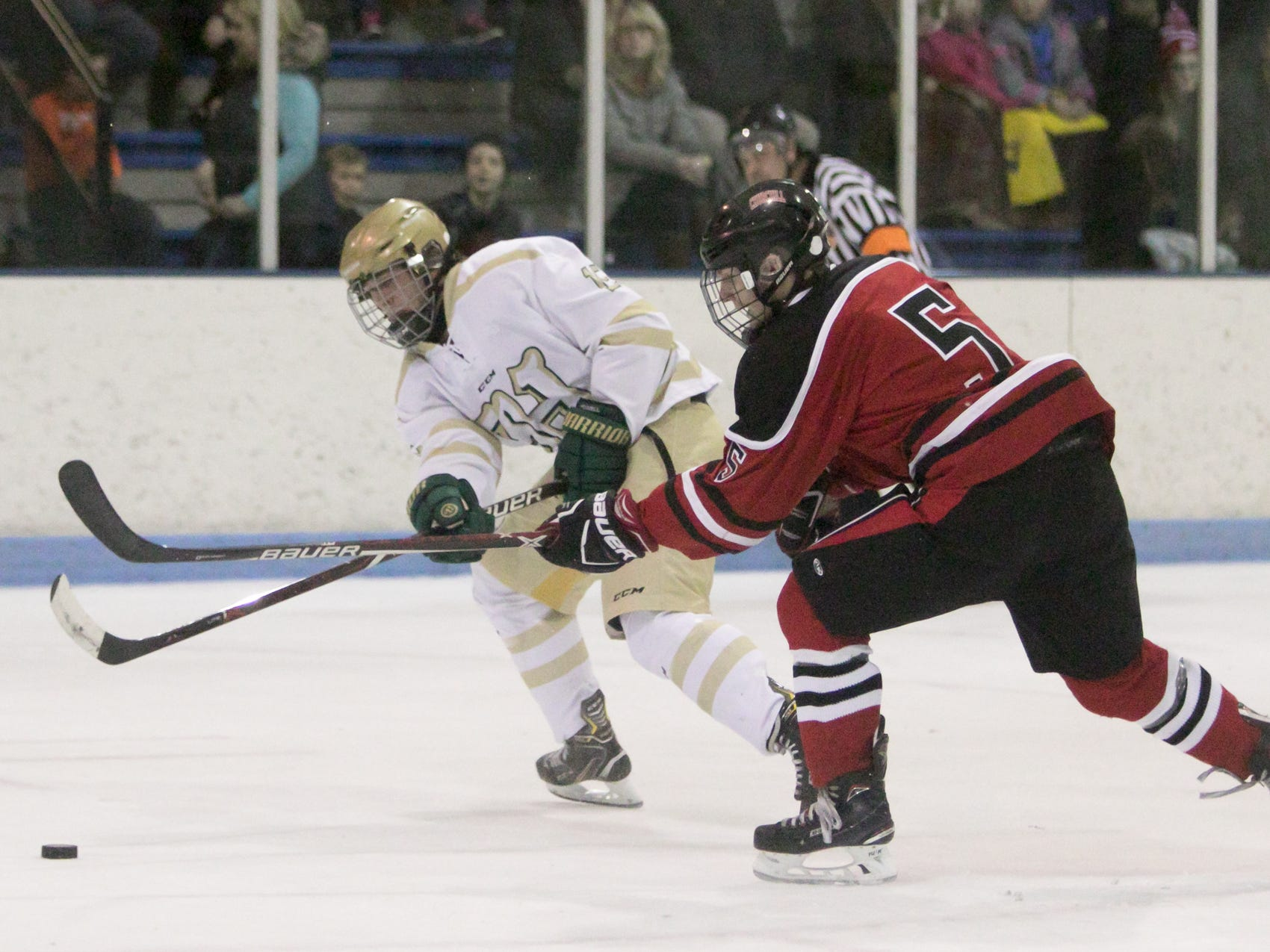 Livonia Churchill's Matt Gibboney (5) defends Howell's Jake Haggerty in the Highlanders' 6-3 victory on Friday, Jan. 4, 2019 at Grand Oaks Ice Arena.