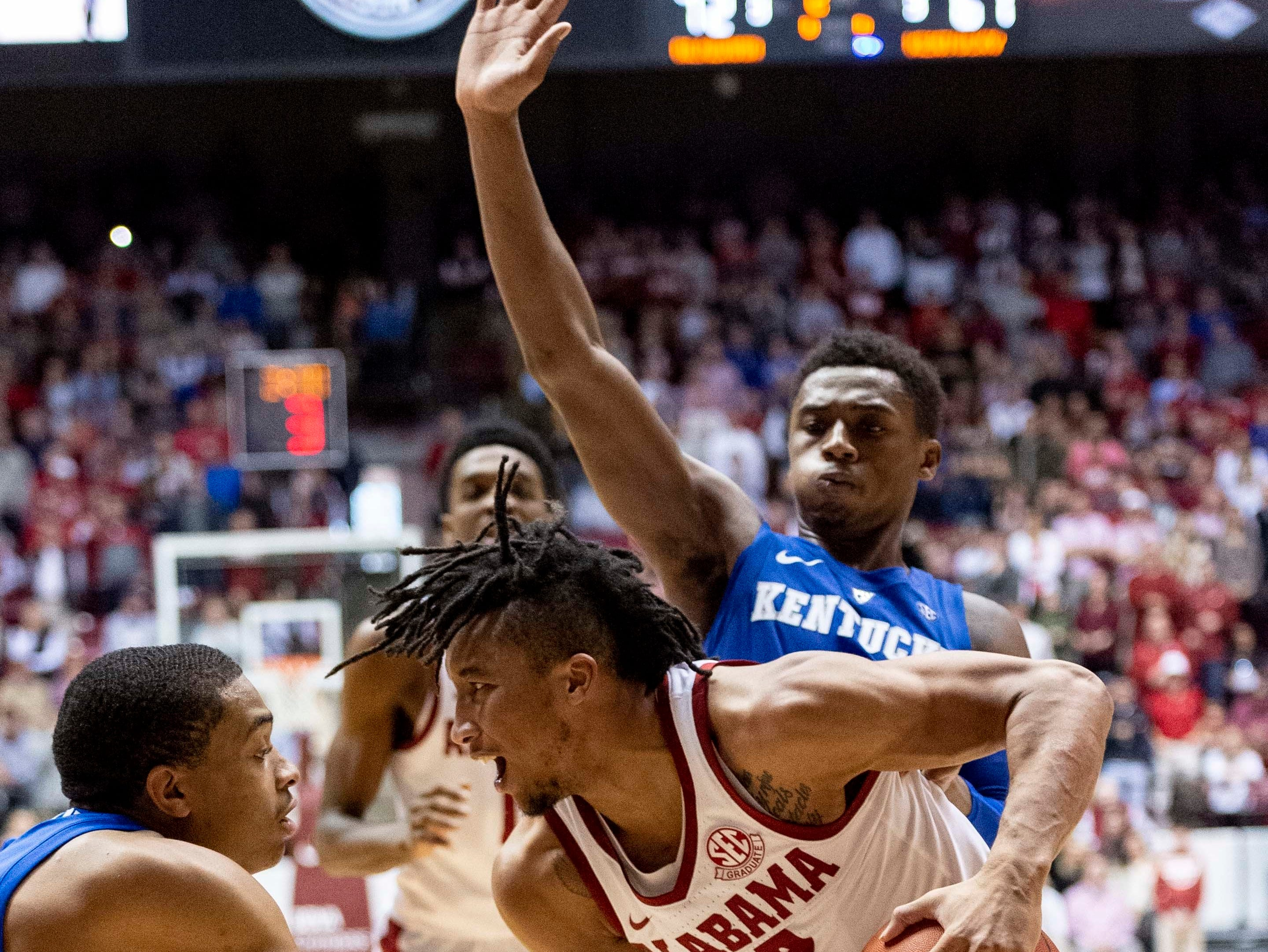 Alabama guard Dazon Ingram (12) battles tight defense from Kentucky guards Keldon Johnson (3), left, and Ashton Hagans (2) during the second half of an NCAA college basketball game, Saturday, Jan. 5, 2019, in Tuscaloosa, Ala.
