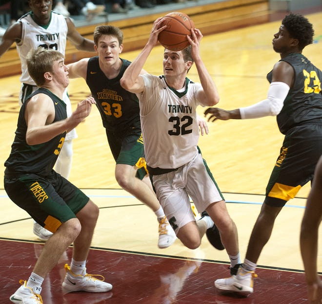 Trinity guard-forward Stan Turnier drives through a crowd of St. Xavier defenders looking to score.