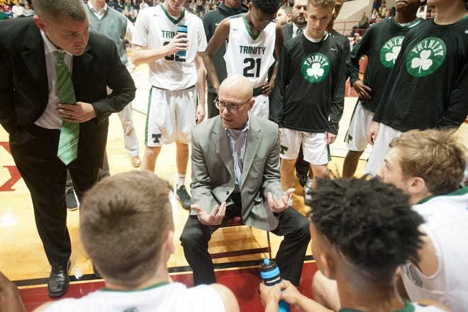 Trinity head basketball coach Mike Szabo talks to his players during a time-out.04 January 2019