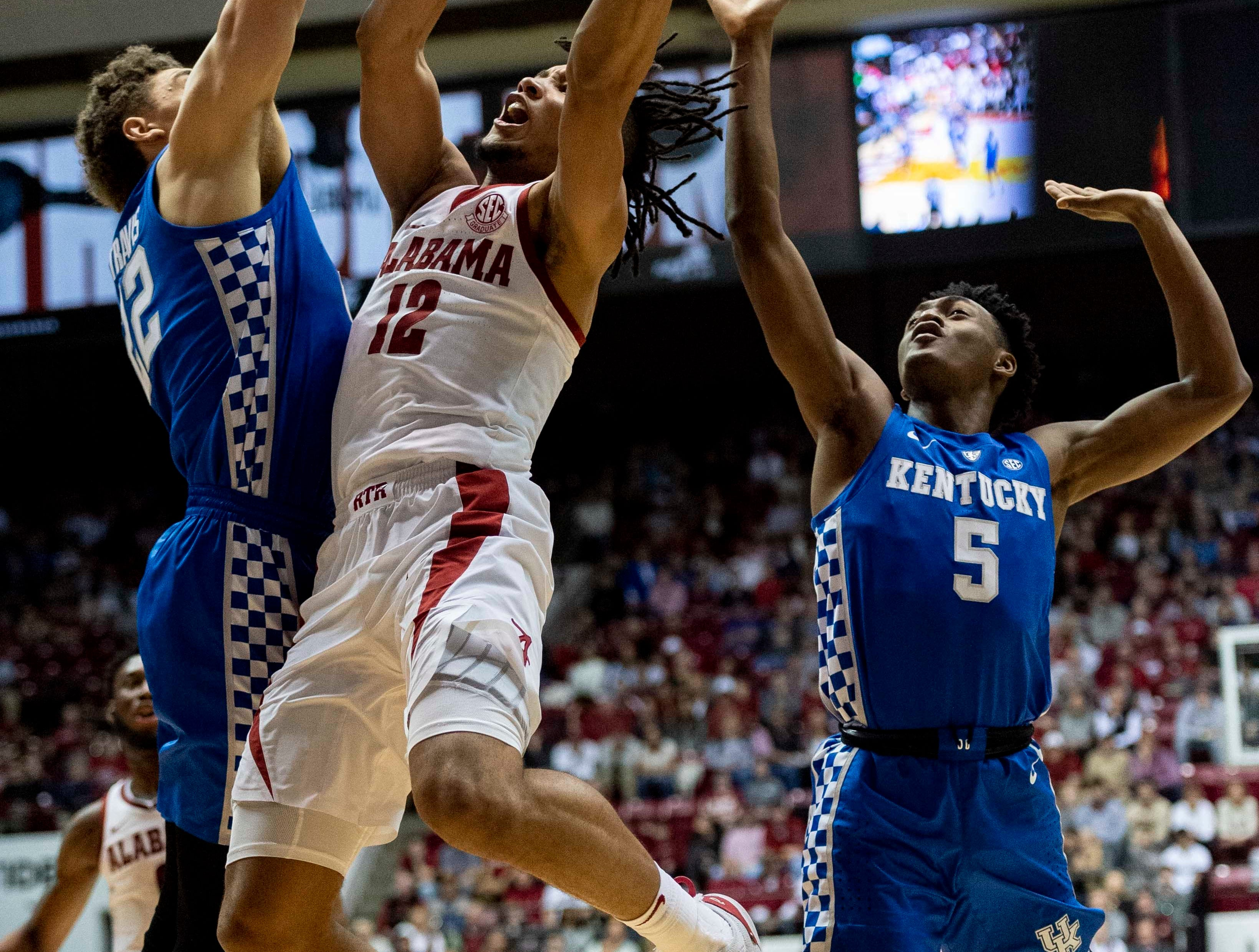 Alabama guard Dazon Ingram (12) gets a shot off between Kentucky forward Reid Travis (22) and guard Immanuel Quickley (5) during the second half of an NCAA college basketball game, Saturday, Jan. 5, 2019, in Tuscaloosa, Ala.