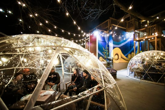 Guests sit in the outdoor patio area at BAD Brewing Company in Mason, Friday, Jan. 4, 2019.  BAD has three heated and lit 'igloos,' or geodesic pop-up domes for wintertime patio seating. Each dome has seating for up to 11 people.