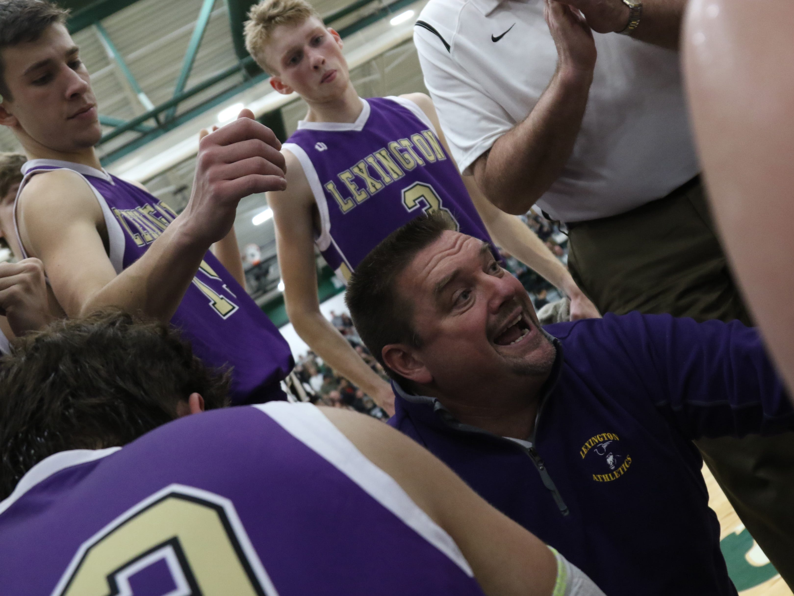 Lexington Boys Basketball coach Scott Hamilton talks to his players during a game at Madison on Friday.