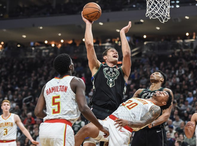 Bucks center Brook Lopez goes up for a shot in the paint and sends Hawks forward Jason Collins to the court on Friday night.
