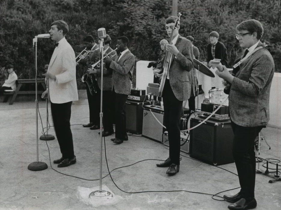 Freddy and the Freeloaders, Musical group, Milwaukee. Fred Bliffert (white jacket) sings in front of the band as other members play on the patio at Atwater Beach bathhouse in Shorewood. Other members are: Randy Byrd, Jack Feldstein, Charlie Brooks, Jim Gaskell and Sam Friedman. Hidden behind the front lines are Jeff Irwin and Pete Leshin.