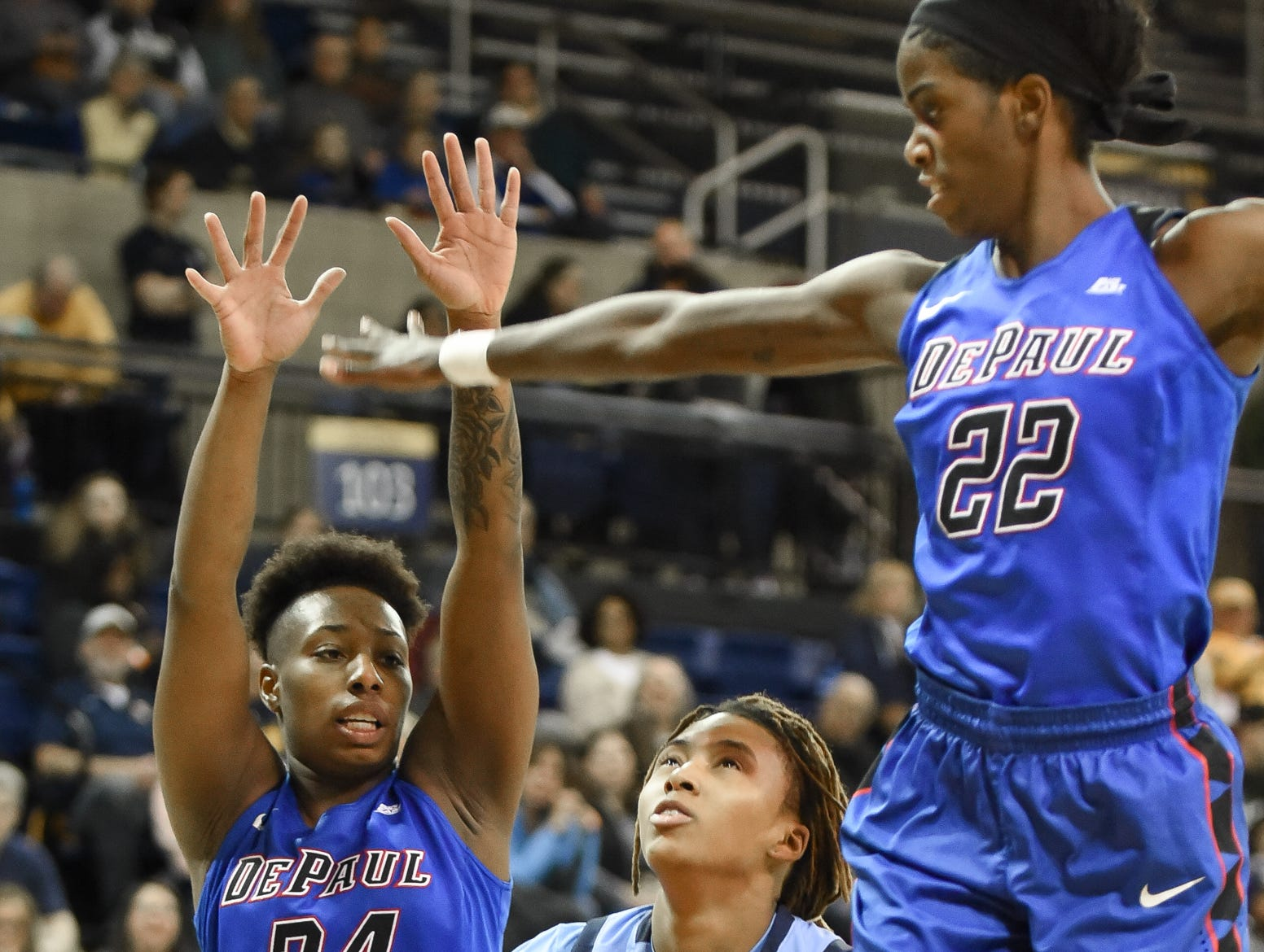 Marquette guard Amani Wilborn fakes DePaul guard Tanita Allen (24) and forward Chante Stonewall before going up for a shot.
