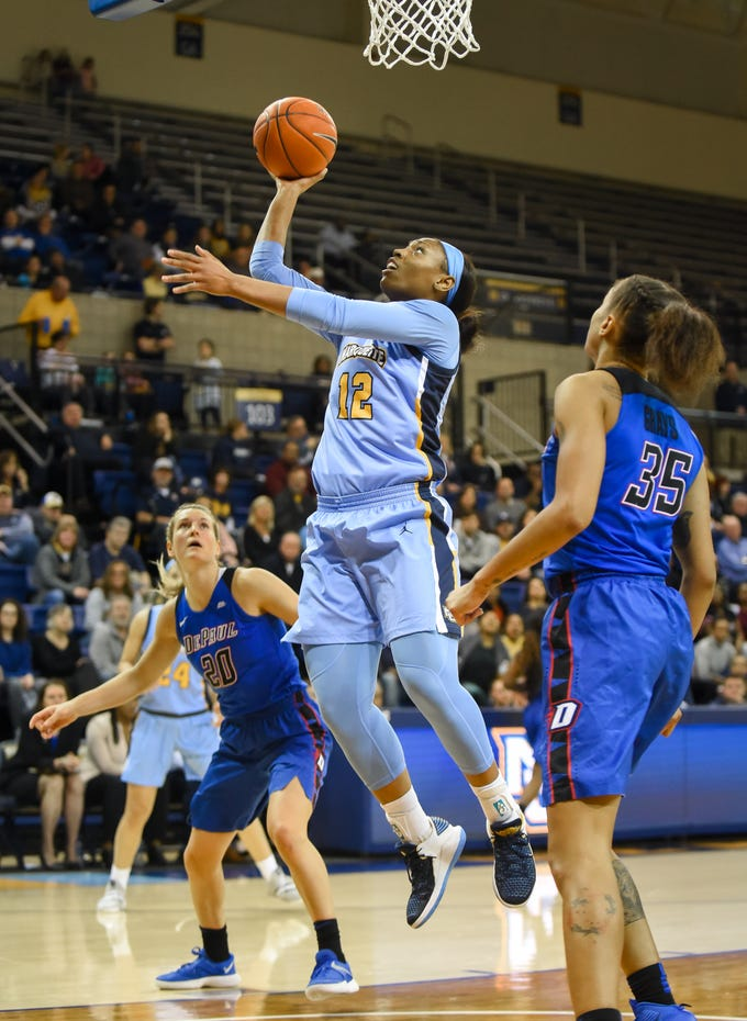 Marquette forward Erika Davenport splits DePaul guard Kelly Campbell (left) and forward Mart'e Grays for a layup.