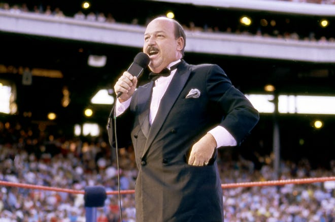 """In this July 31, 1988 photo provided by the WWE, """"Mean"""" Gene Okerlund addresses the crowd before a pro wrestling event in Milwaukee.  Okerlund, who interviewed pro wrestling superstars """"Macho Man"""" Randy Savage, The Ultimate Warrior and Hulk Hogan, has died. He was 76. WWE announced Okerlund's death on its website Wednesday, Jan. 2, 2019. (WWE via AP)"""