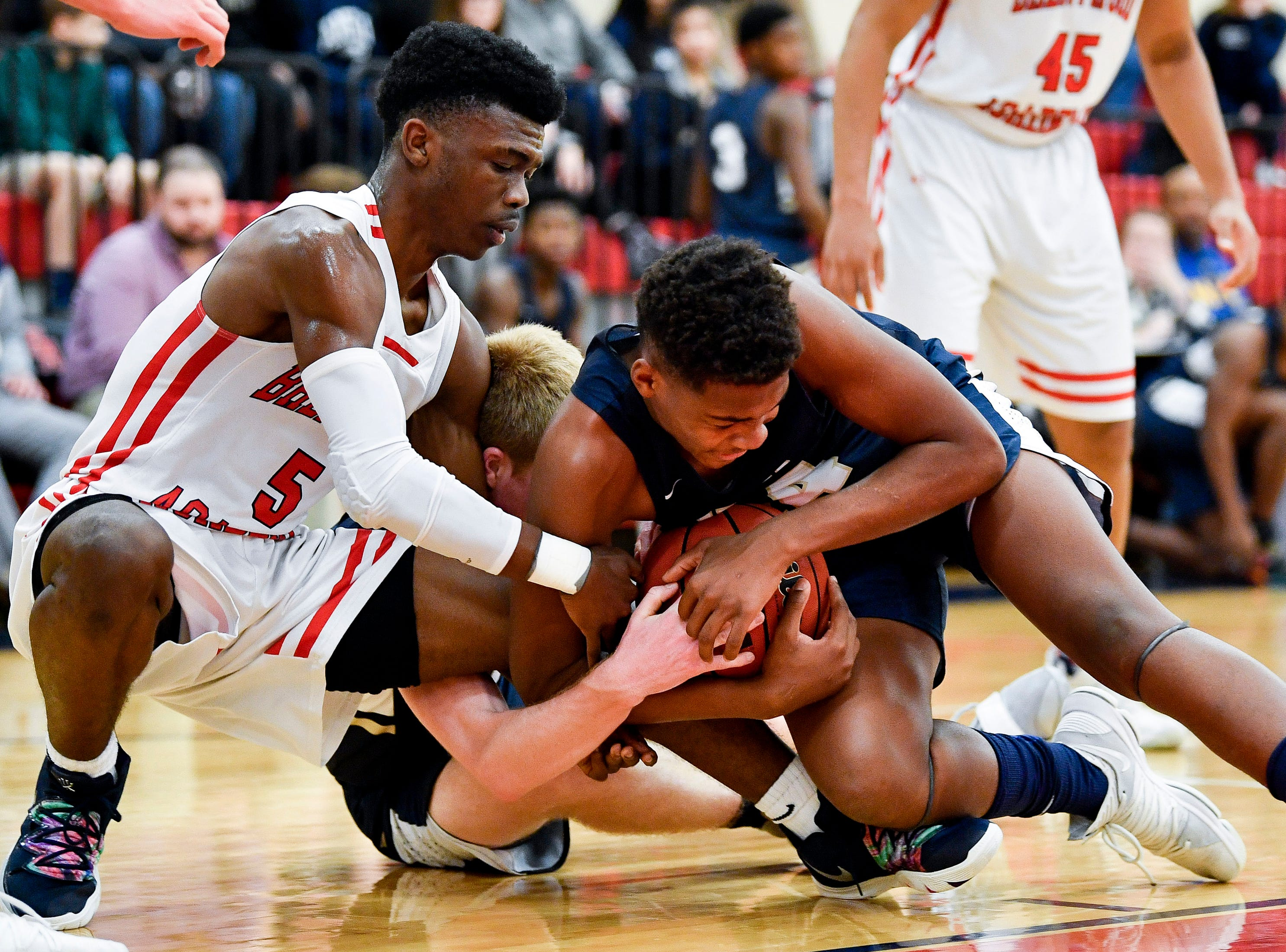 Brentwood Academy's Marcus Fitzgerald jr. (5) fights for the ball with Pope John Paul II's Michael Martini (1) and Ben Nixon (24) during the first half at Brentwood Academy in Brentwood, Tenn., Friday, Jan. 4, 2019.
