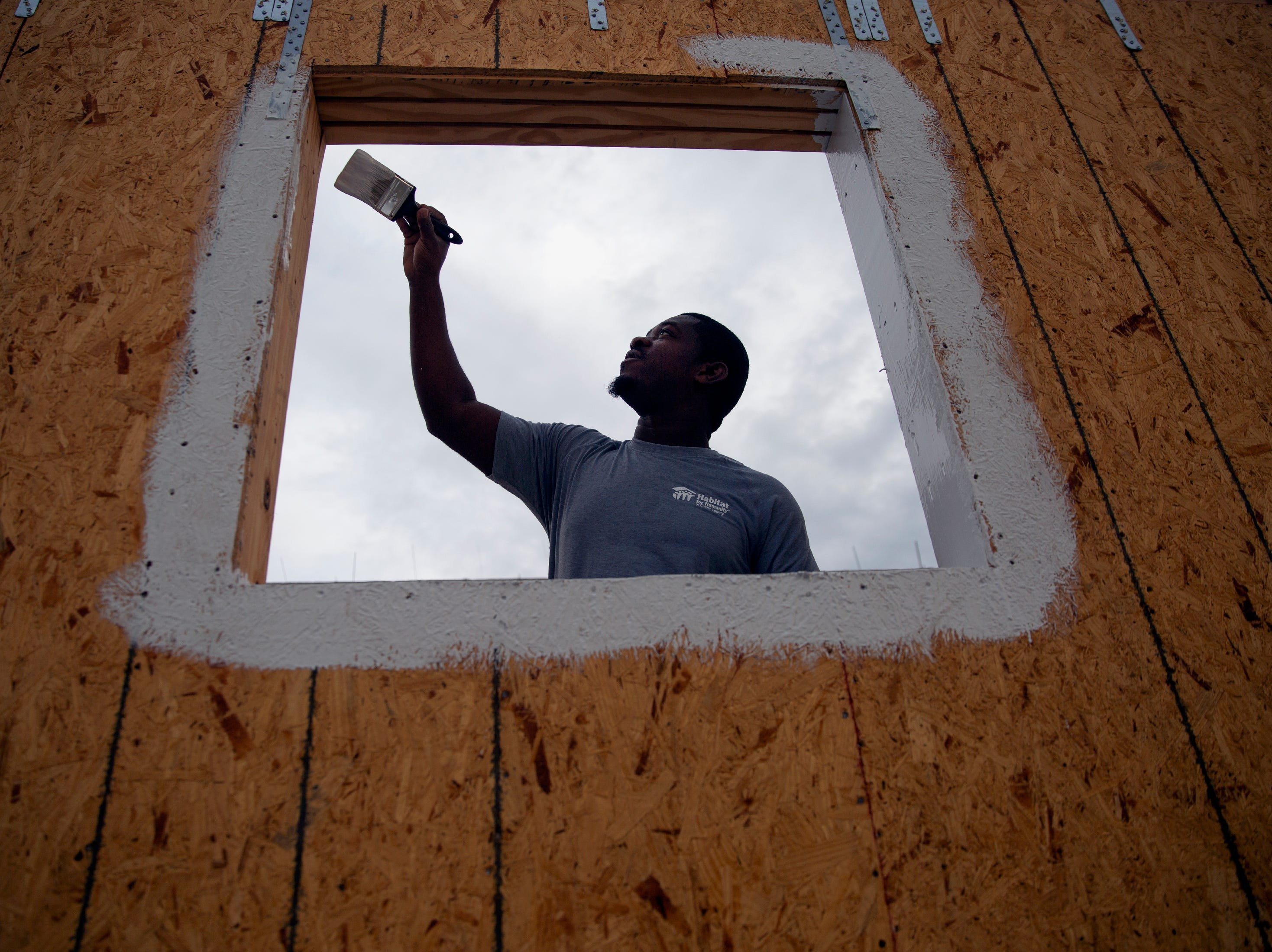 Billy Witte, a site supervisor for Habitat for Humanity of Collier County, applies a protective coating on a window  Saturday, Jan. 5, 2019, in the Dockside neighborhood in East Naples.